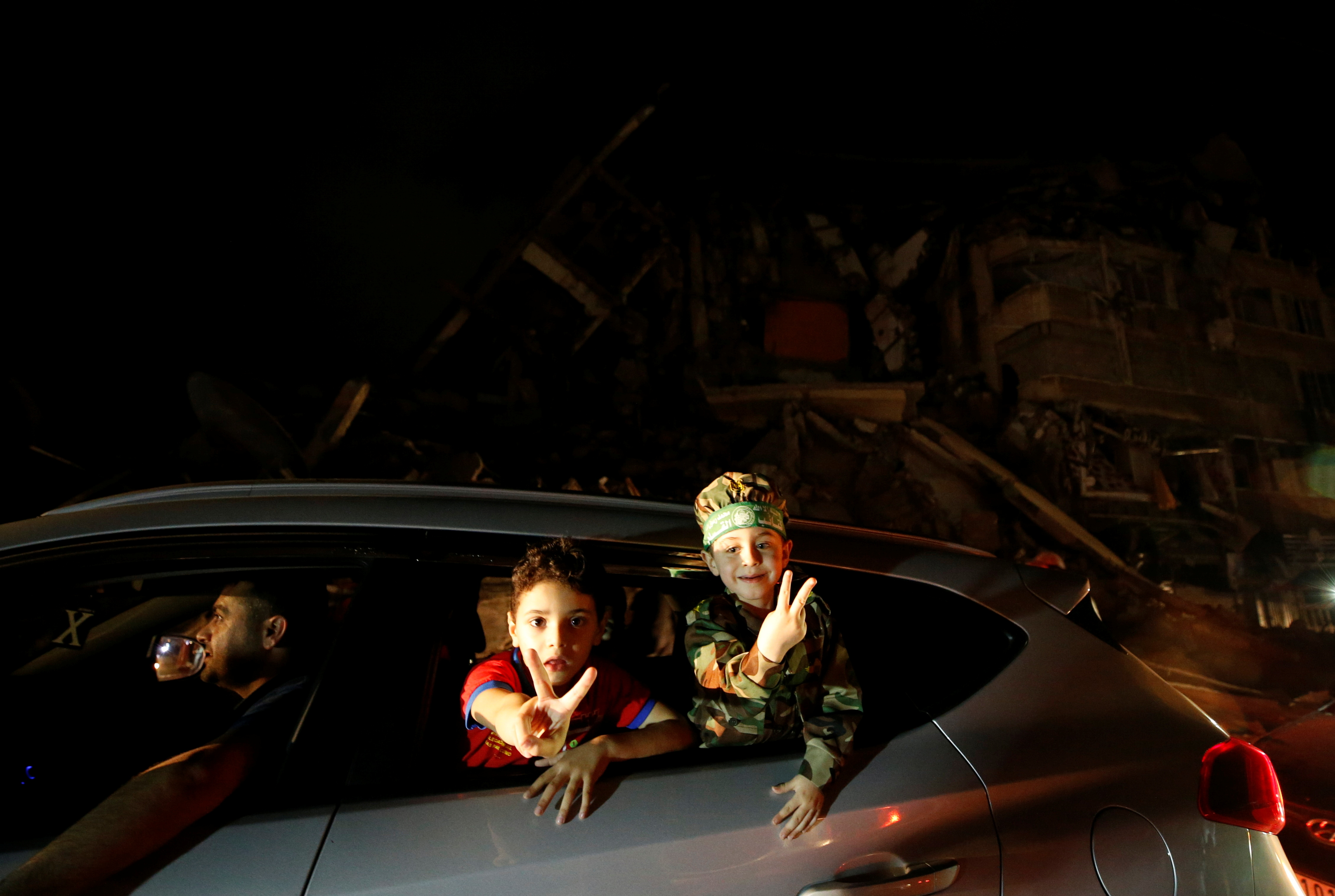 Children gesture from a car driving past the rubble of a damaged building as Palestinians celebrate in the streets following a ceasefire, in Gaza City May 21, 2021. REUTERS/Mohammed Salem