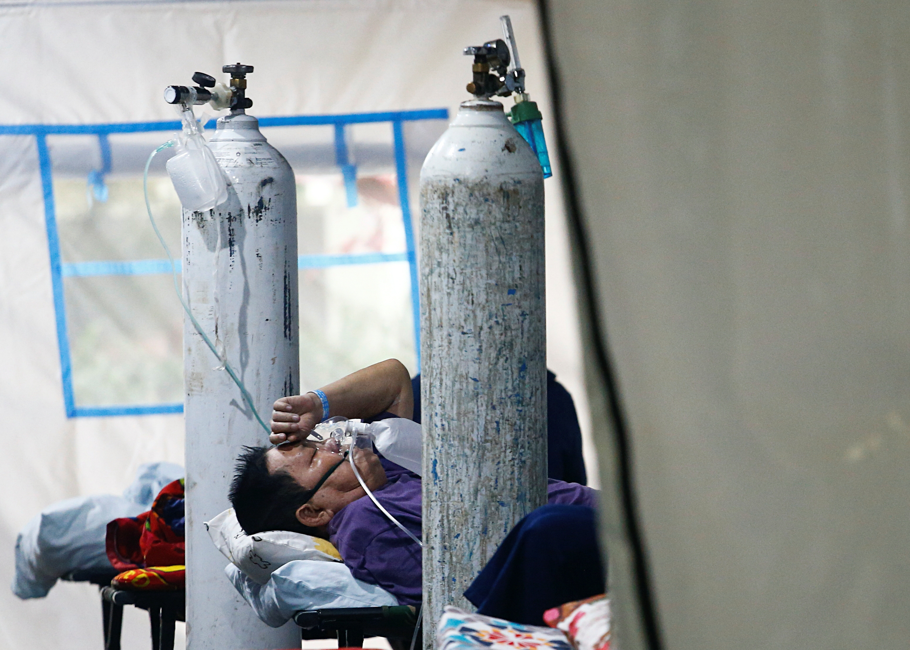 A patient suffering from the coronavirus disease (COVID-19) breaths with a non-rebreather mask in an emergency tent at a hospital in Jakarta, Indonesia, June 24, 2021. REUTERS/Ajeng Dinar Ulfiana