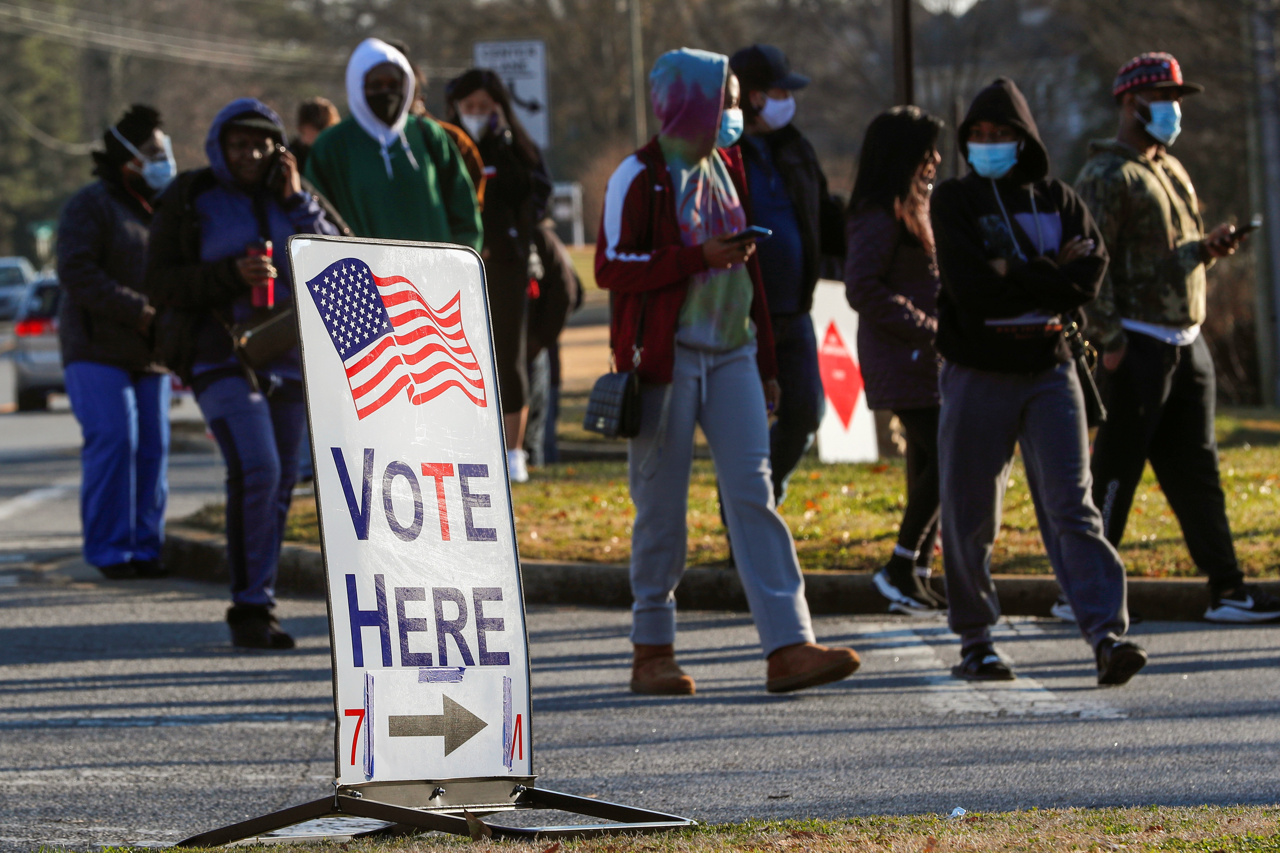 A sign is seen as voters line up for the U.S. Senate run-off election, at a polling location in Marietta, Georgia, U.S., January 5, 2021. REUTERS/Mike Segar