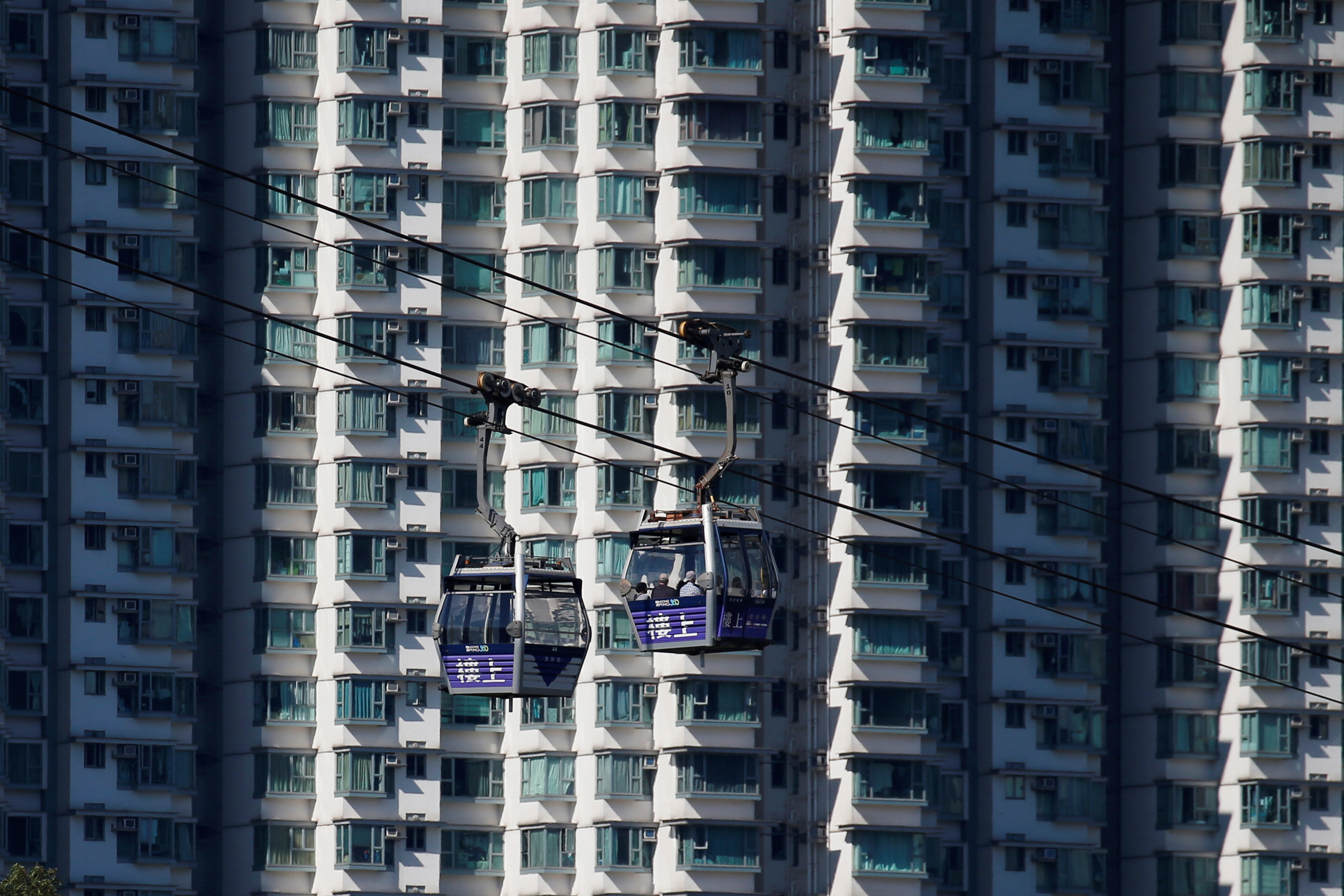 Cable cars move past residential flats at Lantau island in Hong Kong, China May 30, 2018. Picture taken May 30, 2018.     REUTERS/Bobby Yip