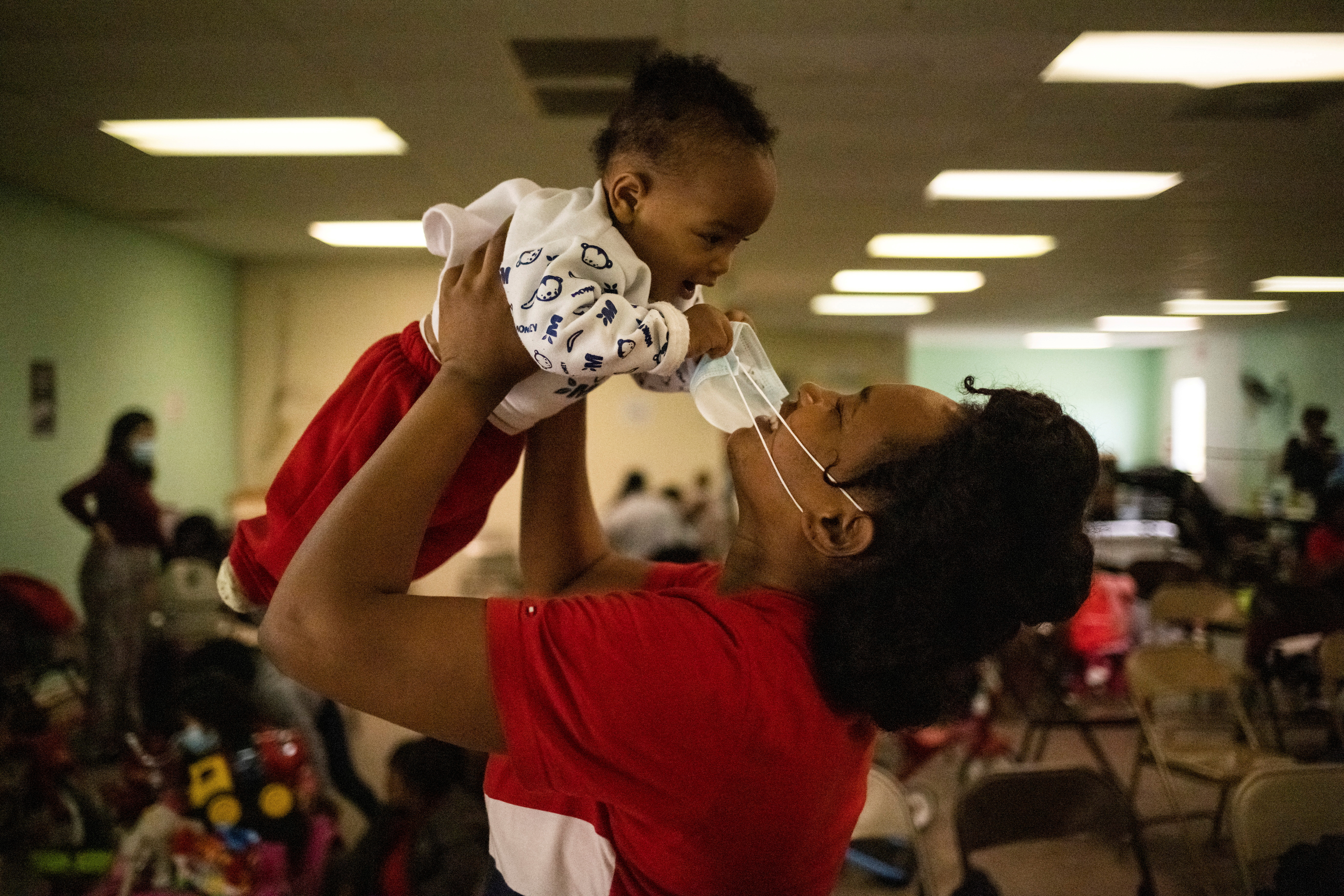 Ley Daxa, a six-month-old migrant boy from Haiti, is lifted into the air by his mother Nadia at the Val Verde Border Humanitarian Coalition after being released from U.S. Customs and Border Protection in Del Rio, Texas, U.S., March 21, 2021. Picture taken on March 21, 2021.   REUTERS/Adrees Latif