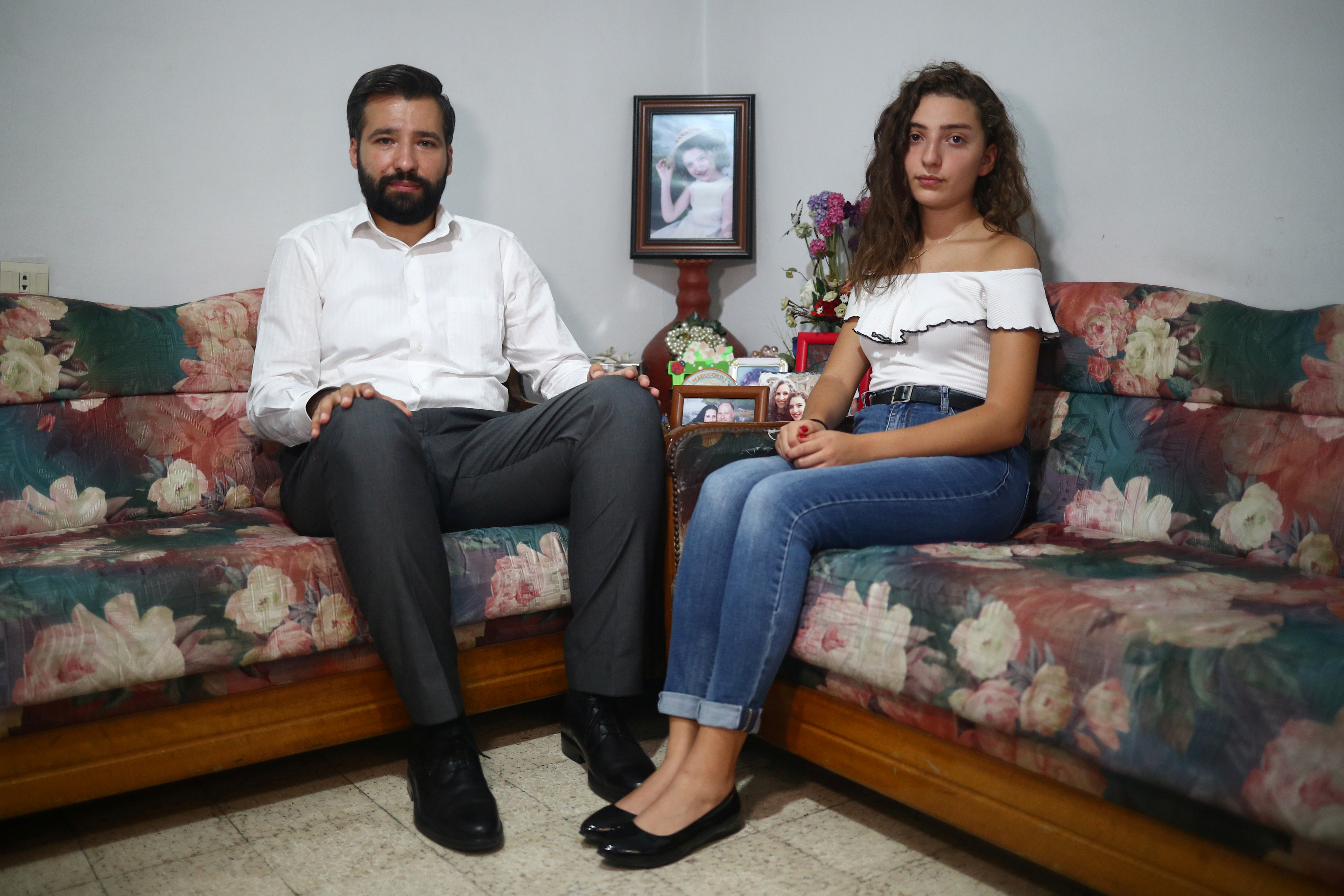 Elie Hasrouty and Tatiana Hasrouty pose for a photograph as they wait for news about their father Ghassan Hasrouty, a missing silo employee, following Tuesday's blast in Beirut's port area, in the family home in Beirut, Lebanon, August 9, 2020. REUTERS/Hannah McKay