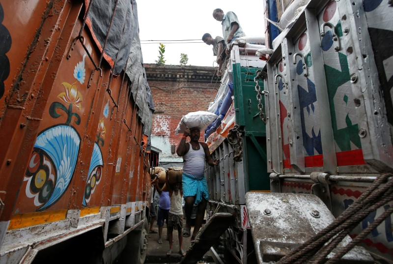 Labourers load sacks of grocery items onto a supply truck at a wholesale market in Kolkata, India, October 12, 2018. REUTERS/Rupak De Chowdhuri/File photo