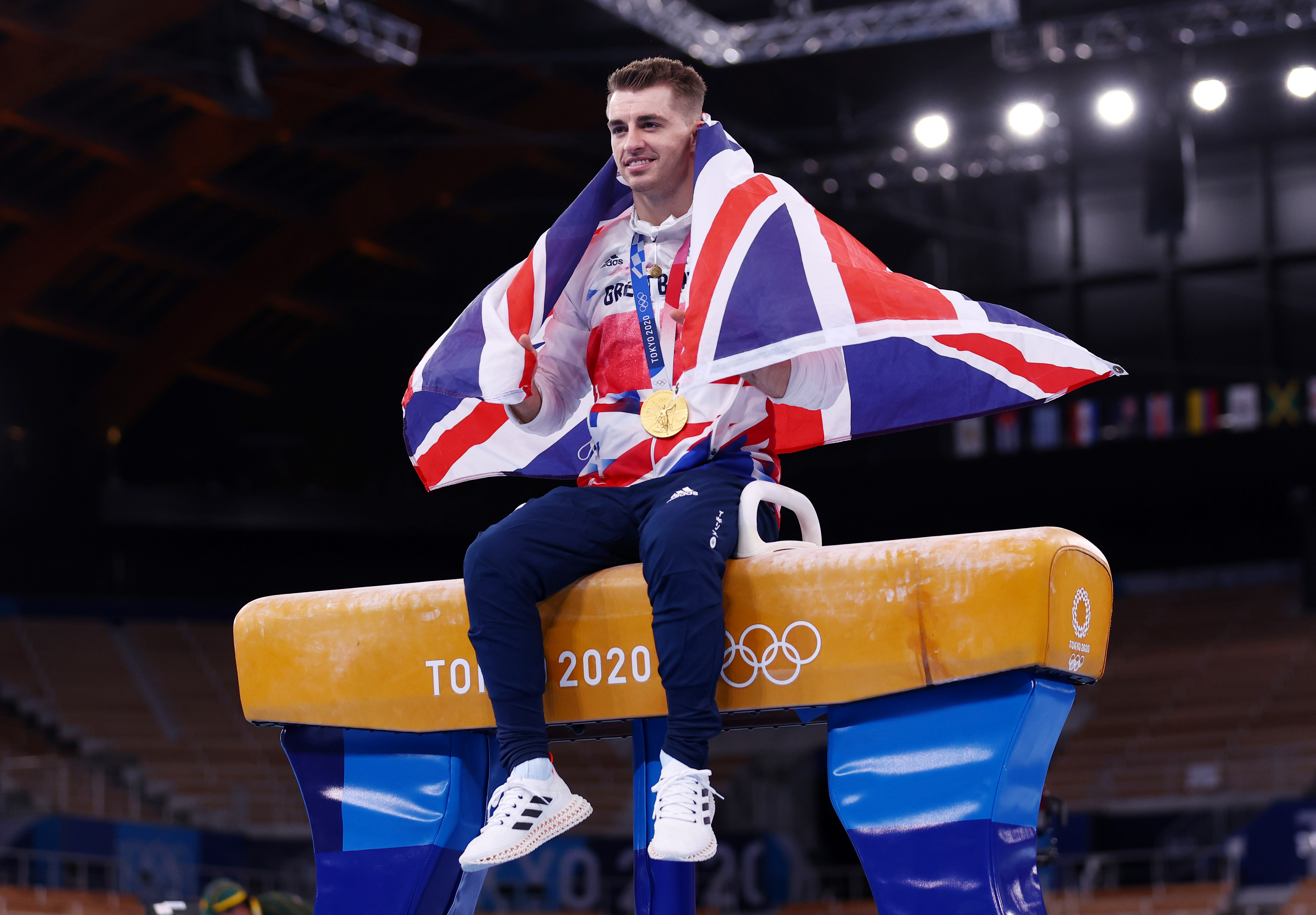 Tokyo 2020 Olympics - Gymnastics - Artistic - Men's Pommel Horse - Medal Ceremony - Ariake Gymnastics Centre, Tokyo, Japan - August 1, 2021. Gold medallist Max Whitlock of Britain poses with his medal whilst sitting on the pommel horse REUTERS/Mike Blake