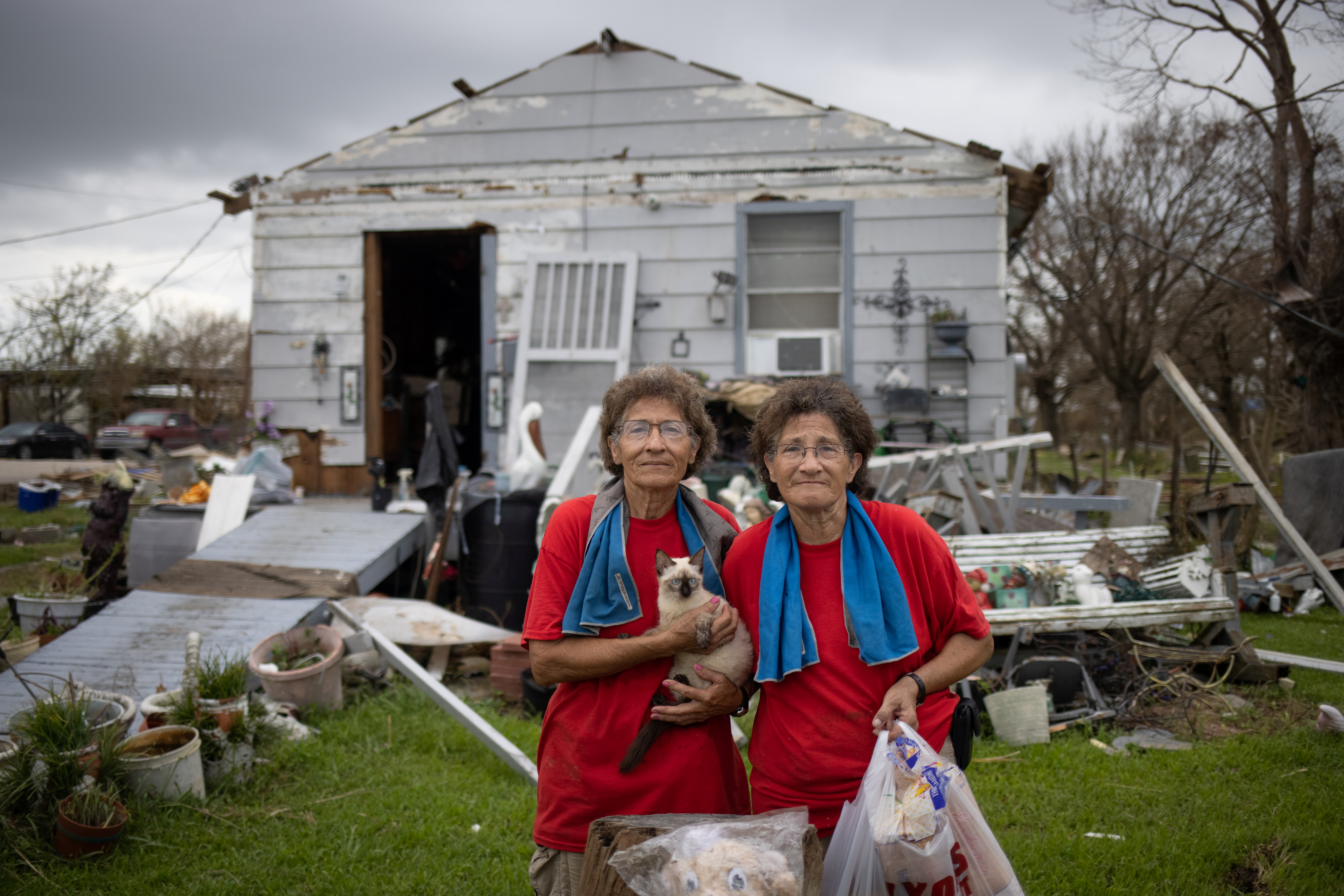Twin sisters Bridget and Rosalie Serigny, 66, hold their cat Frost as they pose for a photograph after returning to their damaged home in the aftermath of Hurricane Ida in Golden Meadow, Louisiana, U.S., September 1, 2021. The sisters said the category 4 hurricane destroyed the roof of their house and chicken coop. REUTERS/Adrees Latif