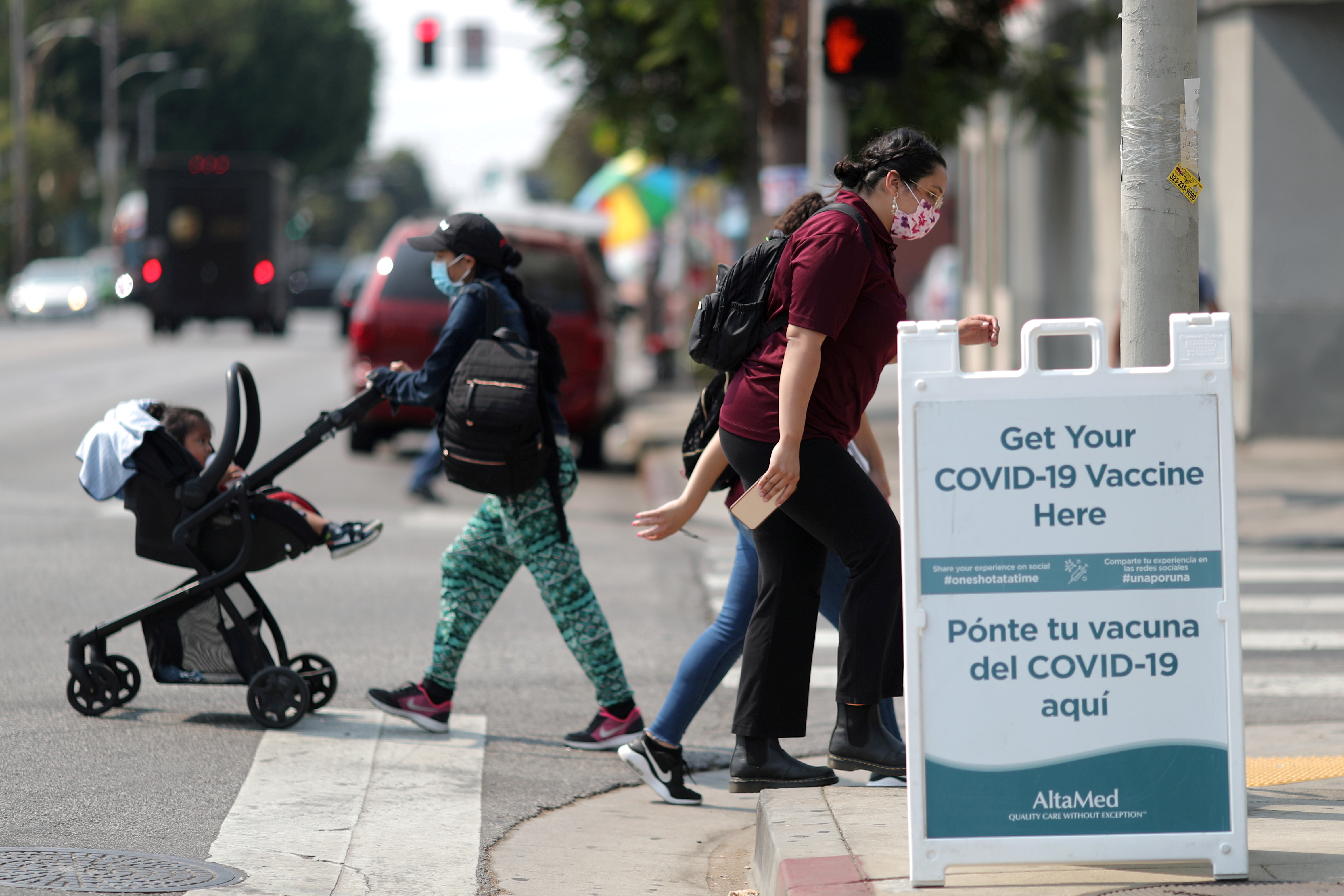 People walk past a sign for a coronavirus disease (COVID-19) vaccination clinic in Los Angeles, California, U.S., August 17, 2021. REUTERS/Lucy Nicholson/File Photo