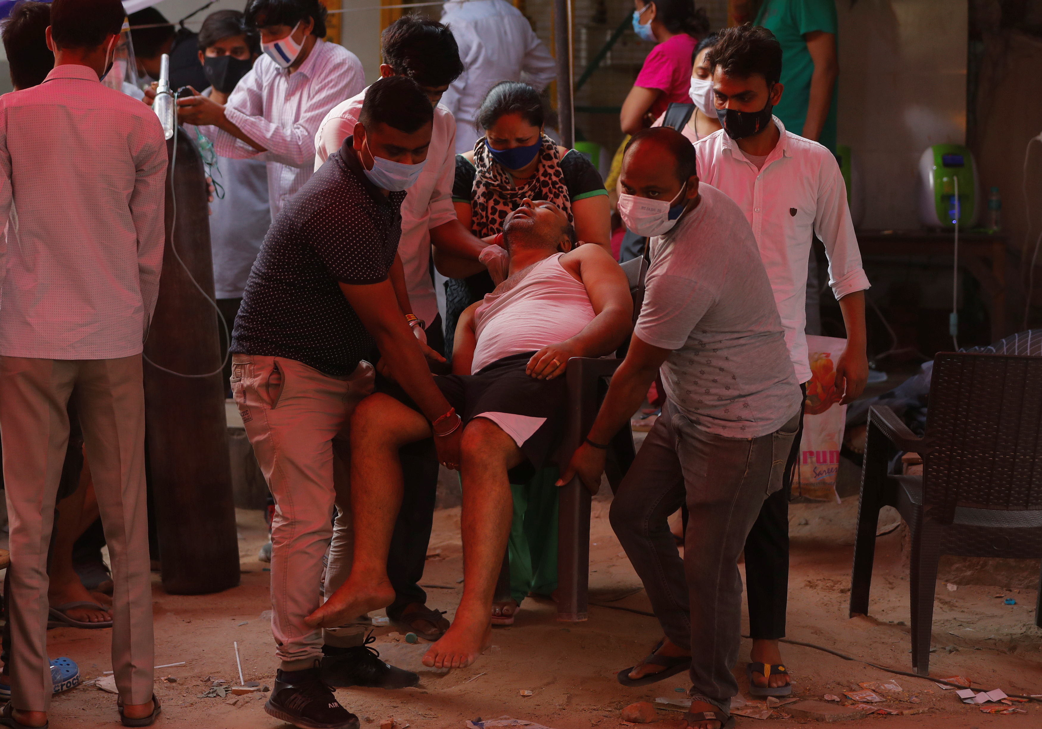People carry the father of Manisha Bashu towards an ambulance, after he felt unconsicous while receiving oxygen support for free at a Gurudwara (Sikh temple), amidst the spread of coronavirus disease (COVID-19), in Ghaziabad, India, April 30, 2021. REUTERS/Adnan Abidi