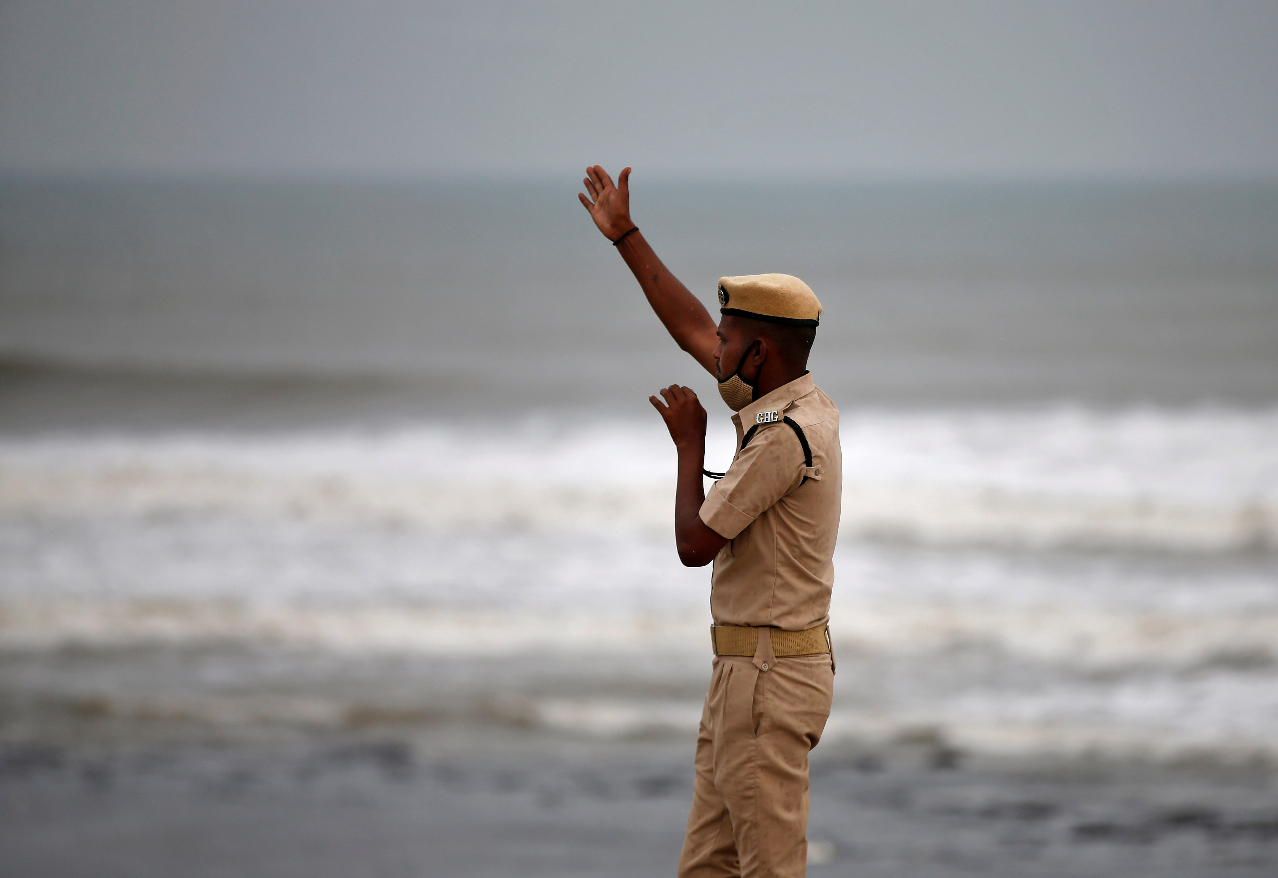 A policeman directs people to leave as waves approach the shore ahead of Cyclone Tauktae in Veraval in the western state of Gujarat, India, May 17, 2021. REUTERS/Amit Dave