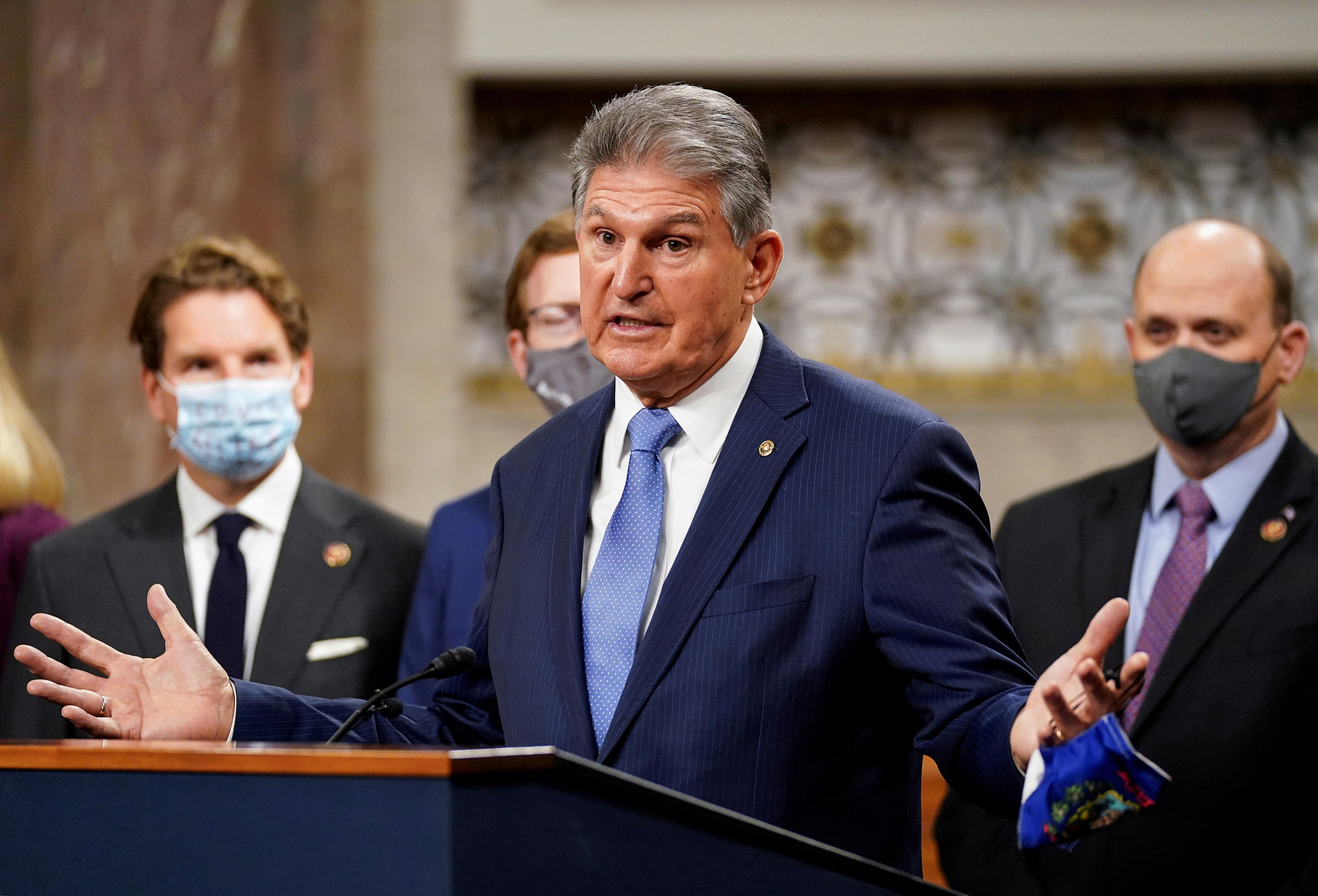 U.S. Senator Joe Manchin (D-WVA) removes his mask to speak as bipartisan members of the Senate and House gather to announce a framework for fresh coronavirus disease (COVID-19) relief legislation at a news conference on Capitol Hill in Washington, U.S., December 1, 2020. REUTERS/Kevin Lamarque/File Photo