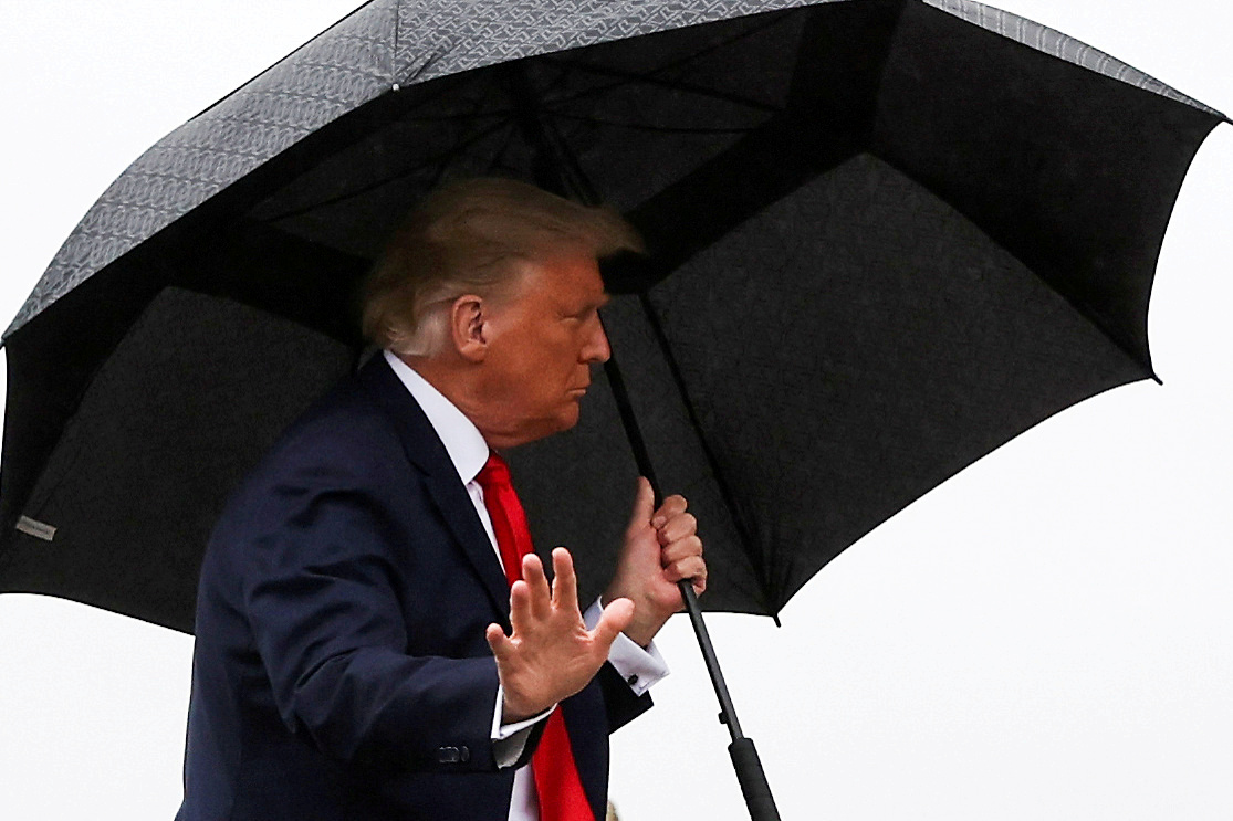 U.S. President Donald Trump carries an umbrella while boarding Air Force One at Joint Base Andrews, Maryland, U.S., October 12, 2020. REUTERS/Jonathan Ernst