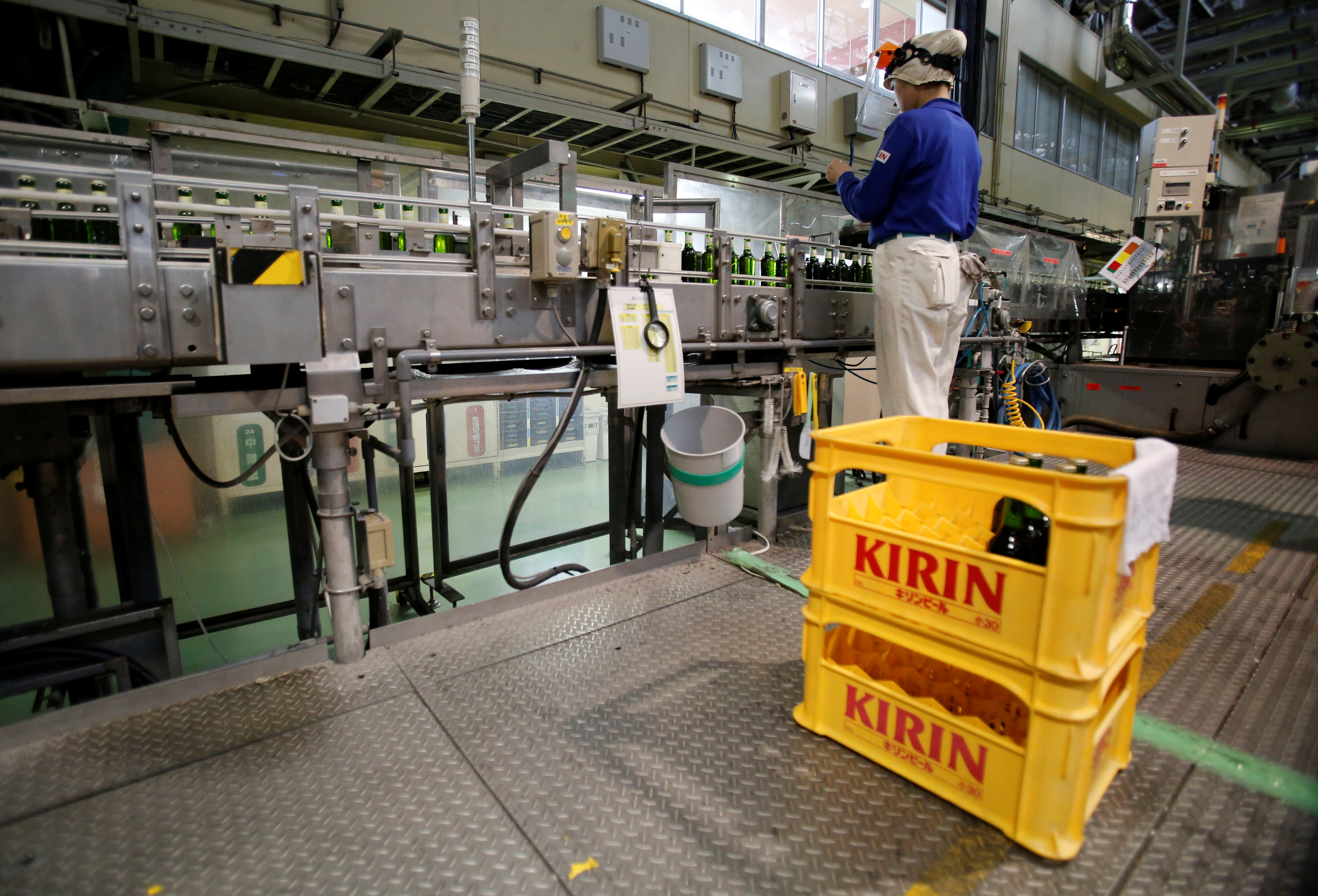 An employee works at a beer production line at Japanese brewer Kirin Holdings' factory in Toride, Ibaraki Prefecture, Japan July 14, 2017. REUTERS/Kim Kyung-Noon