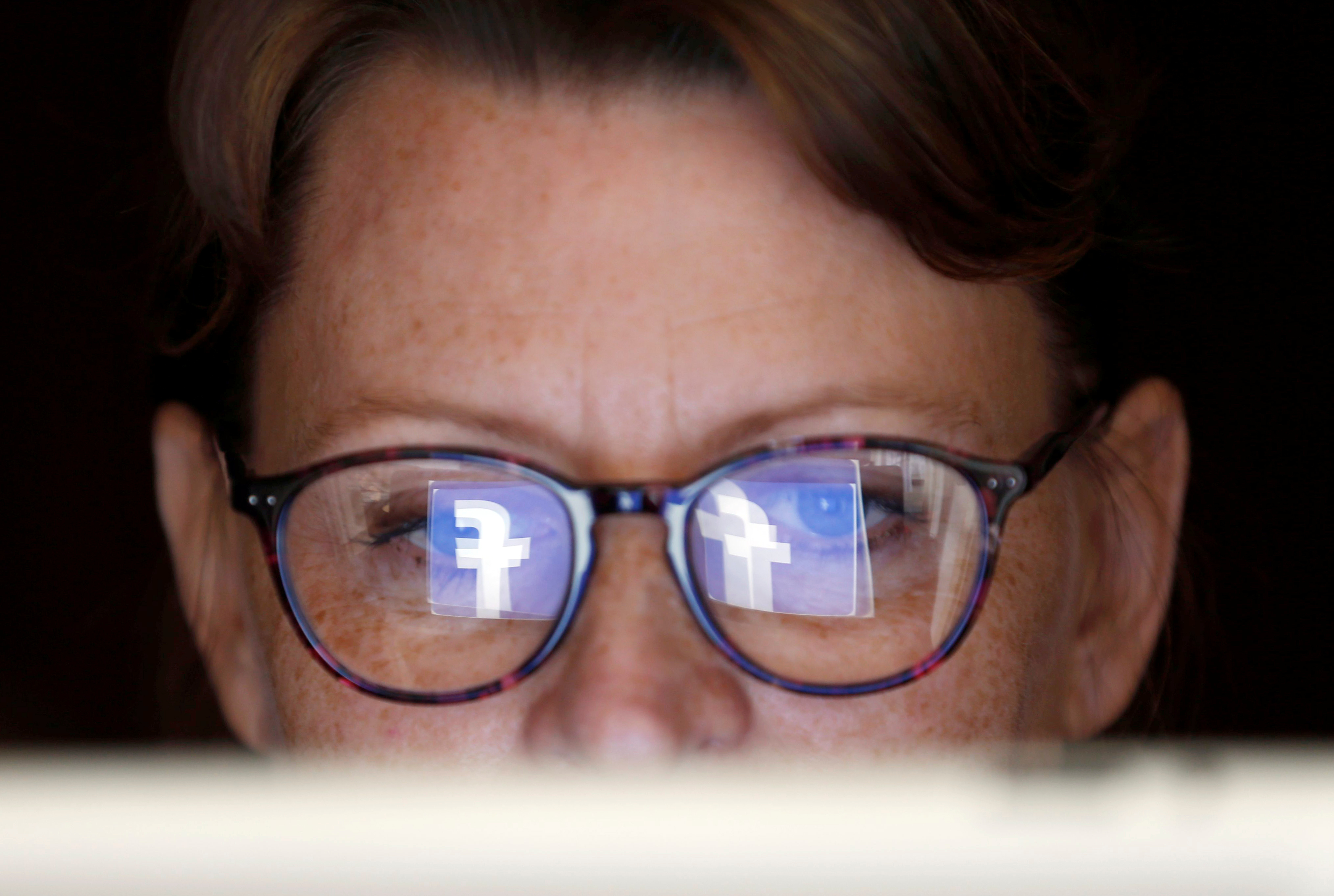 The Facebook logo is reflected on a woman's glasses in this photo illustration taken June 3, 2018.