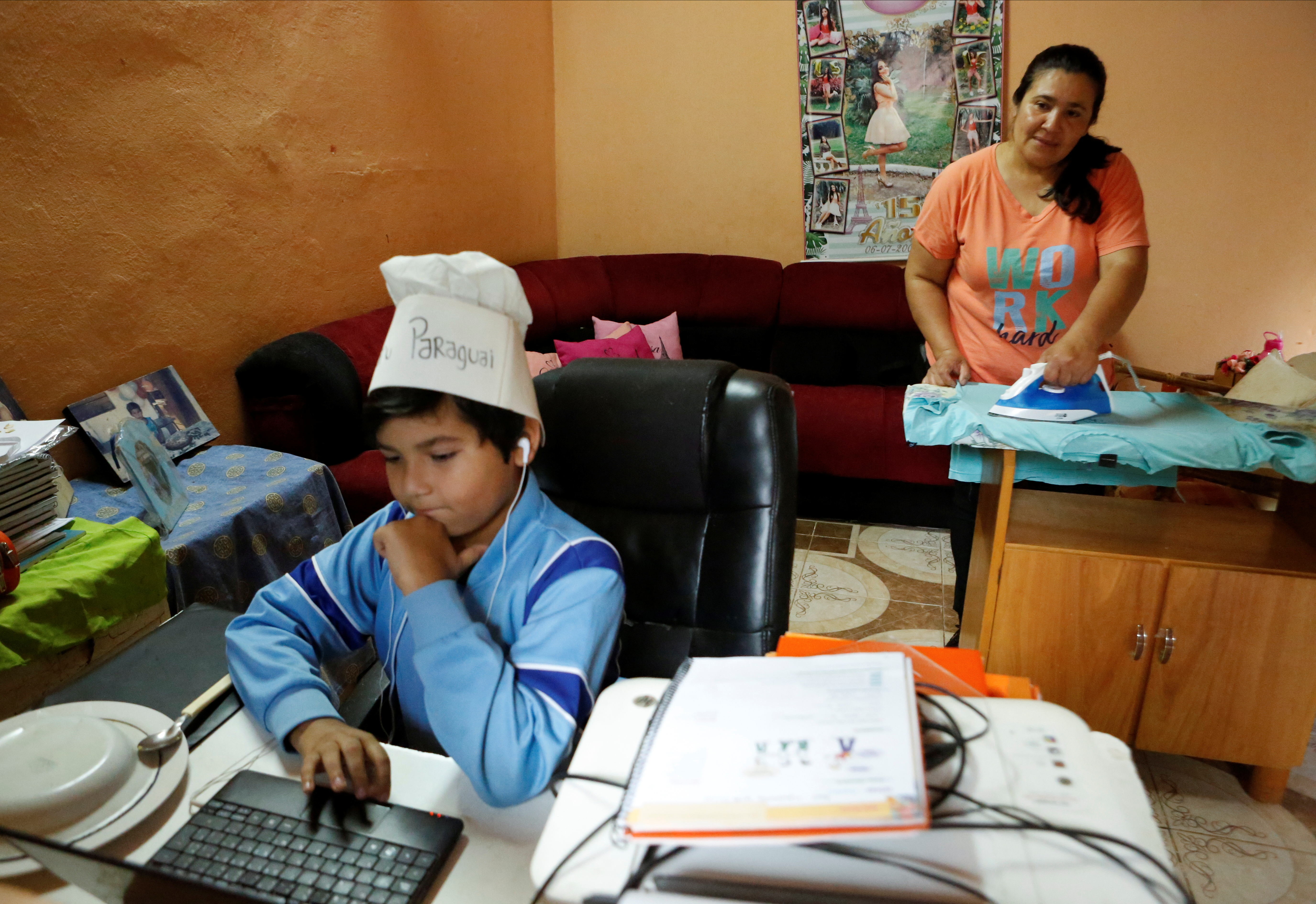Rosa Maidana, 45, irons clothes as her son Luis Maidana, 9, attends the virtual school for distance learning, as the coronavirus disease (COVID-19) restrictions continue, in San Antonio, Paraguay September 3, 2021. Latin America's mothers are lagging behind in the pandemic of economic recovery, returning to the labor force more slowly than men, in a trend that experts say could set back female labor force participation for a decade across the region. Picture taken September 3, 2021. REUTERS/Cesar Olmedo
