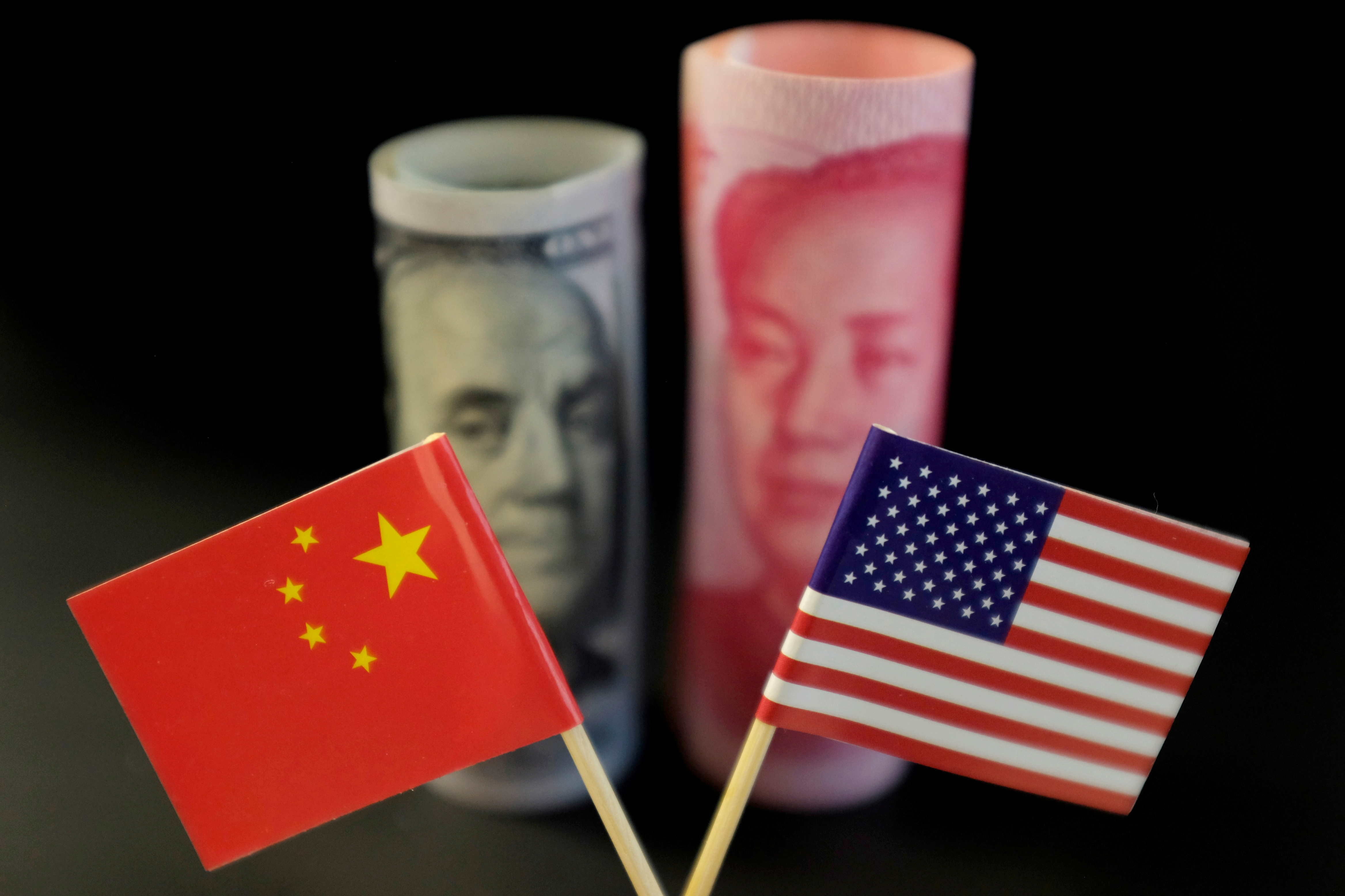 U.S. and Chinese flags are seen in front of a U.S. dollar banknote featuring American founding father Benjamin Franklin and a China's yuan banknote featuring late Chinese chairman Mao Zedong in this illustration picture taken May 20, 2019. REUTERS/Jason Lee/Illustration/File Photo