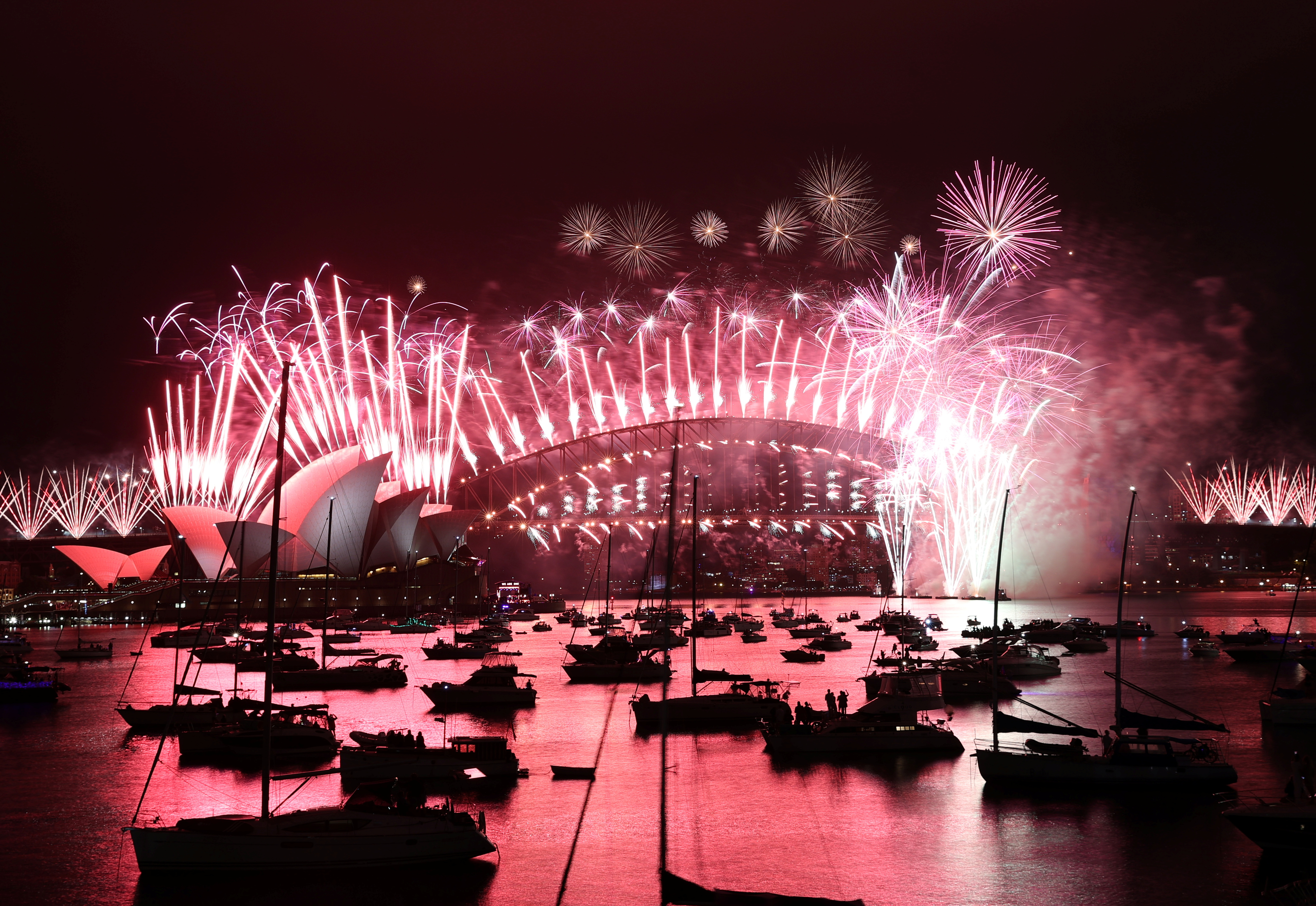 Fireworks explode over the Sydney Opera House and Sydney Harbour Bridge during downsized New Year's Eve celebrations due to an outbreak of the coronavirus disease (COVID-19) in Sydney, Australia, January 1, 2021. REUTERS/Loren Elliott