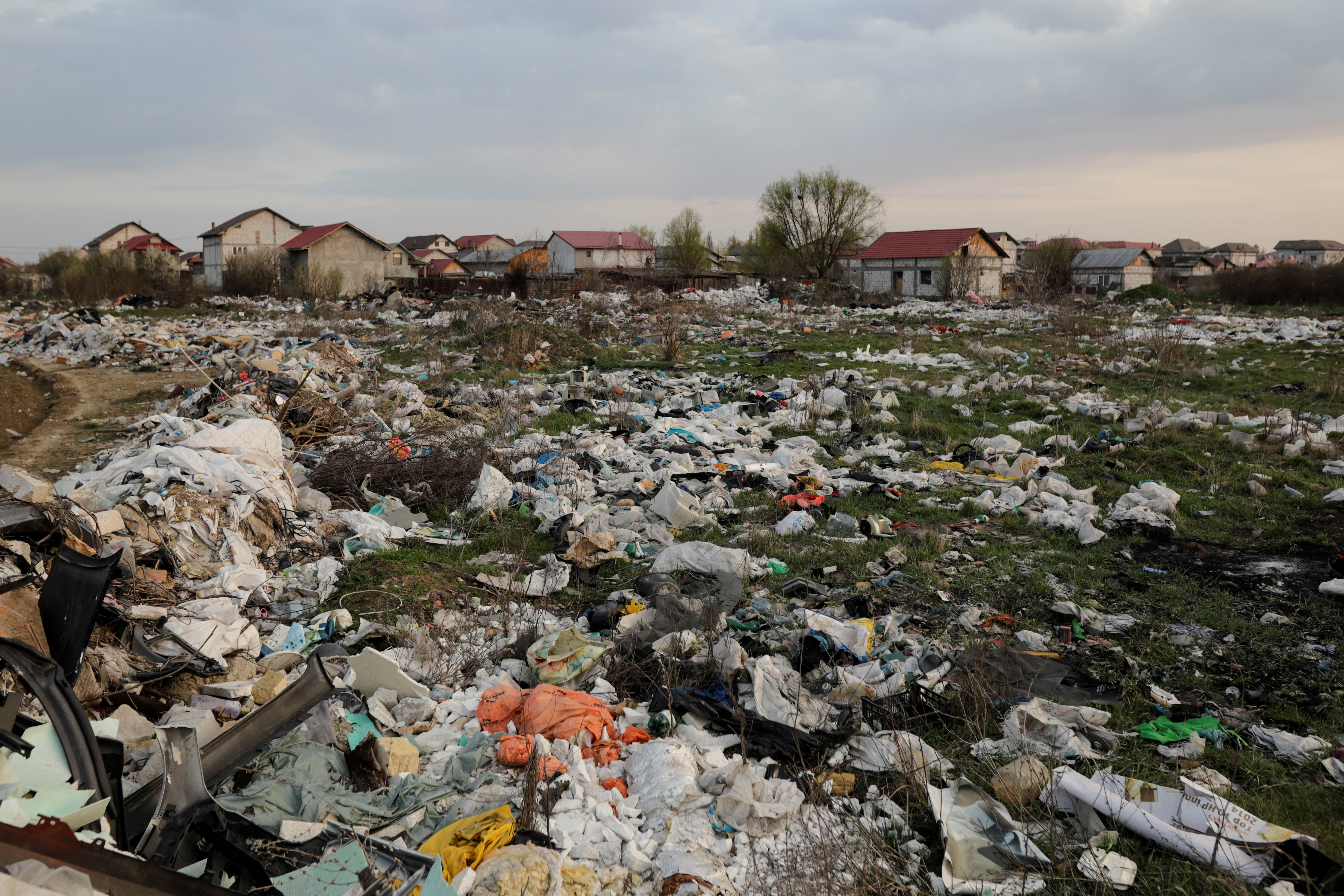 Trash dumped close to houses is scattered on a field, in Bolintin-Vale, Giurgiu, Romania, April 2, 2021.  Inquam Photos/George Calin via REUTERS