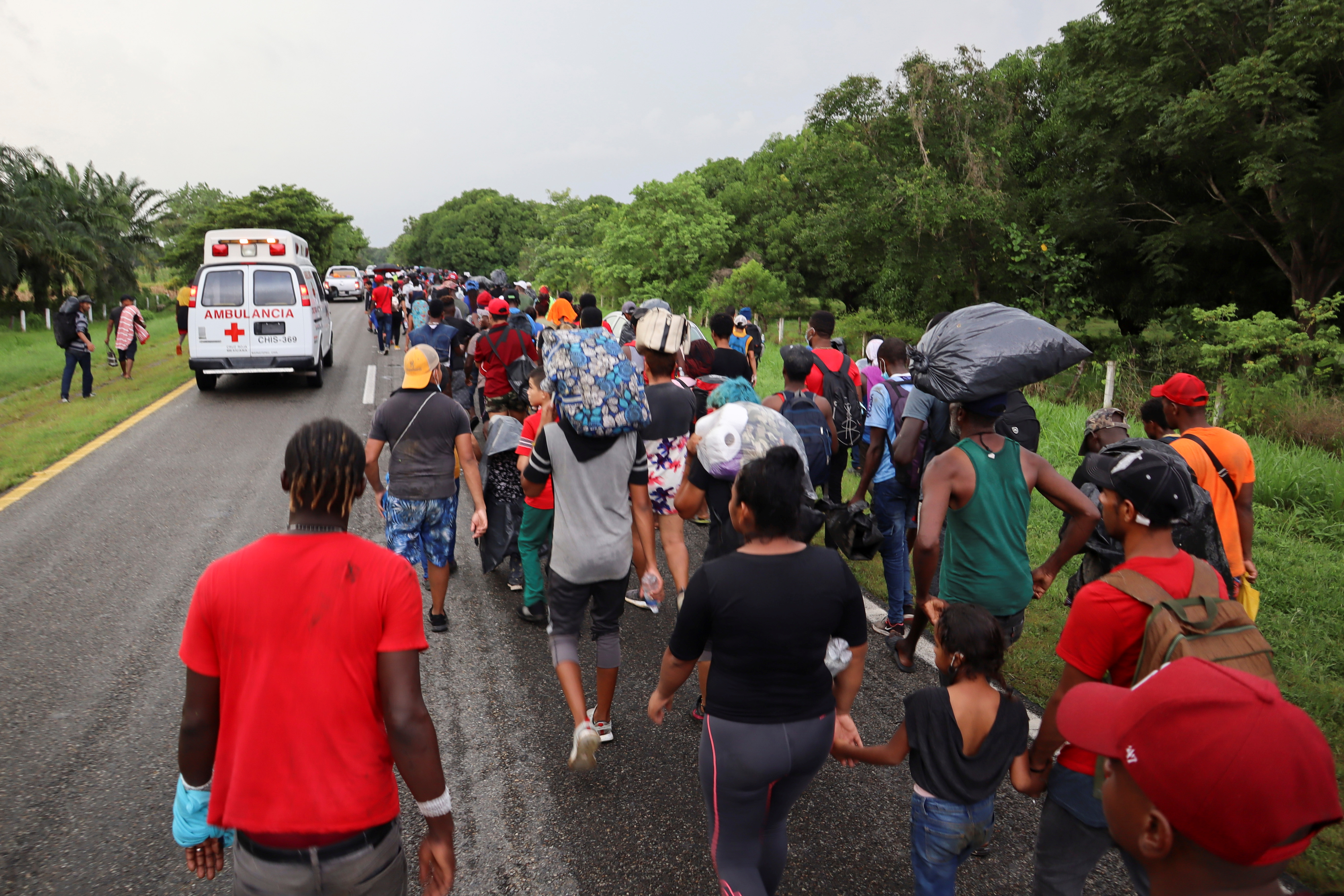 Migrants and asylum seekers from Central America and the Caribbean walk in a caravan headed to the Mexican capital to apply for asylum and refugee status, on a highway near Escuintla, in Chiapas state, Mexico August 29, 2021. REUTERS/Jose Torres