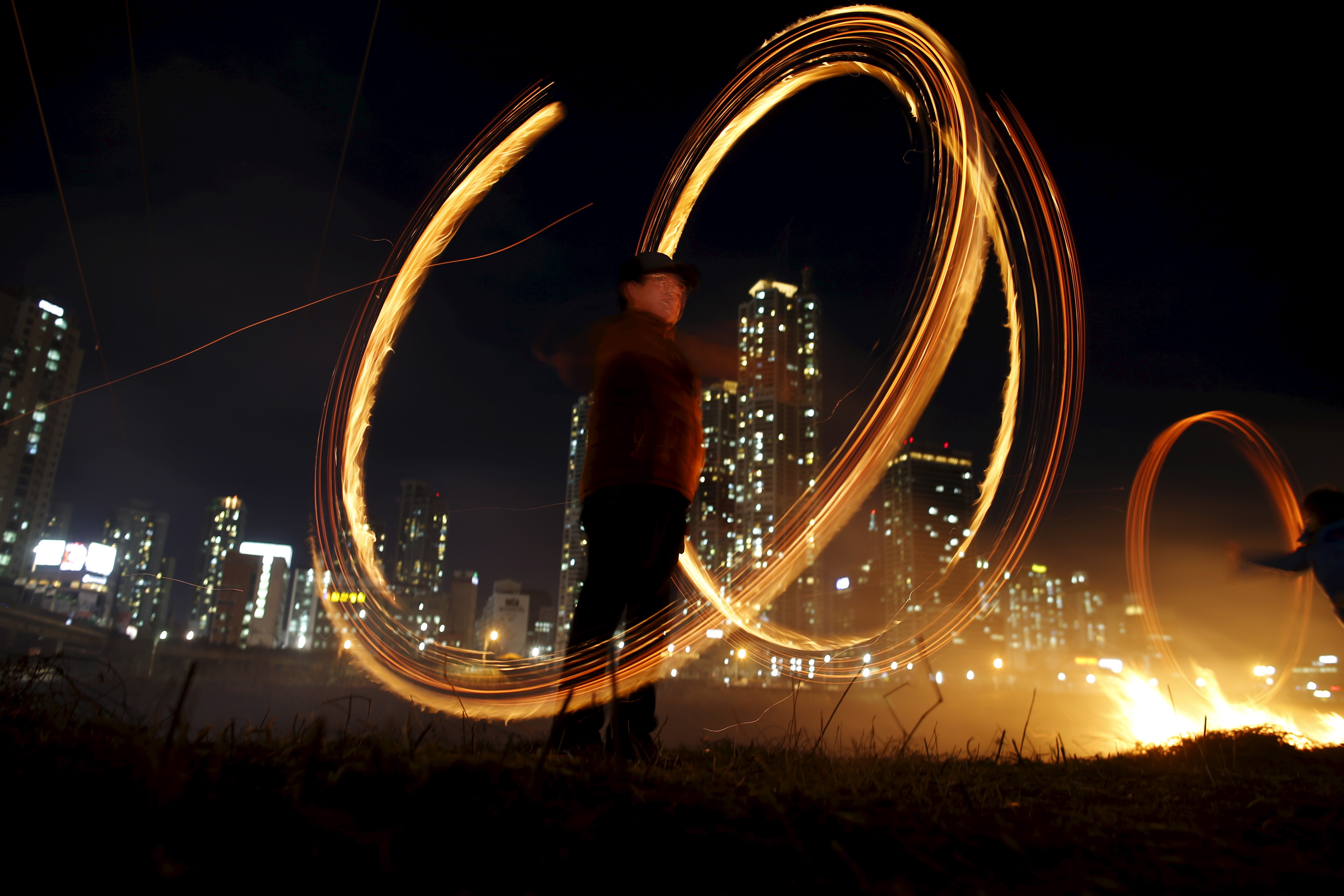 A participant whirls cans filled with burning wood chips during a celebration ahead of