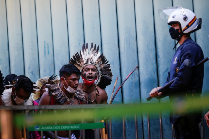 A police officer stands guard, while Indigenous Brazilians protest to defend demarcation of indigenous lands next the National Congress in Brasilia, Brazil June 16, 2021. REUTERS/Adriano Machado