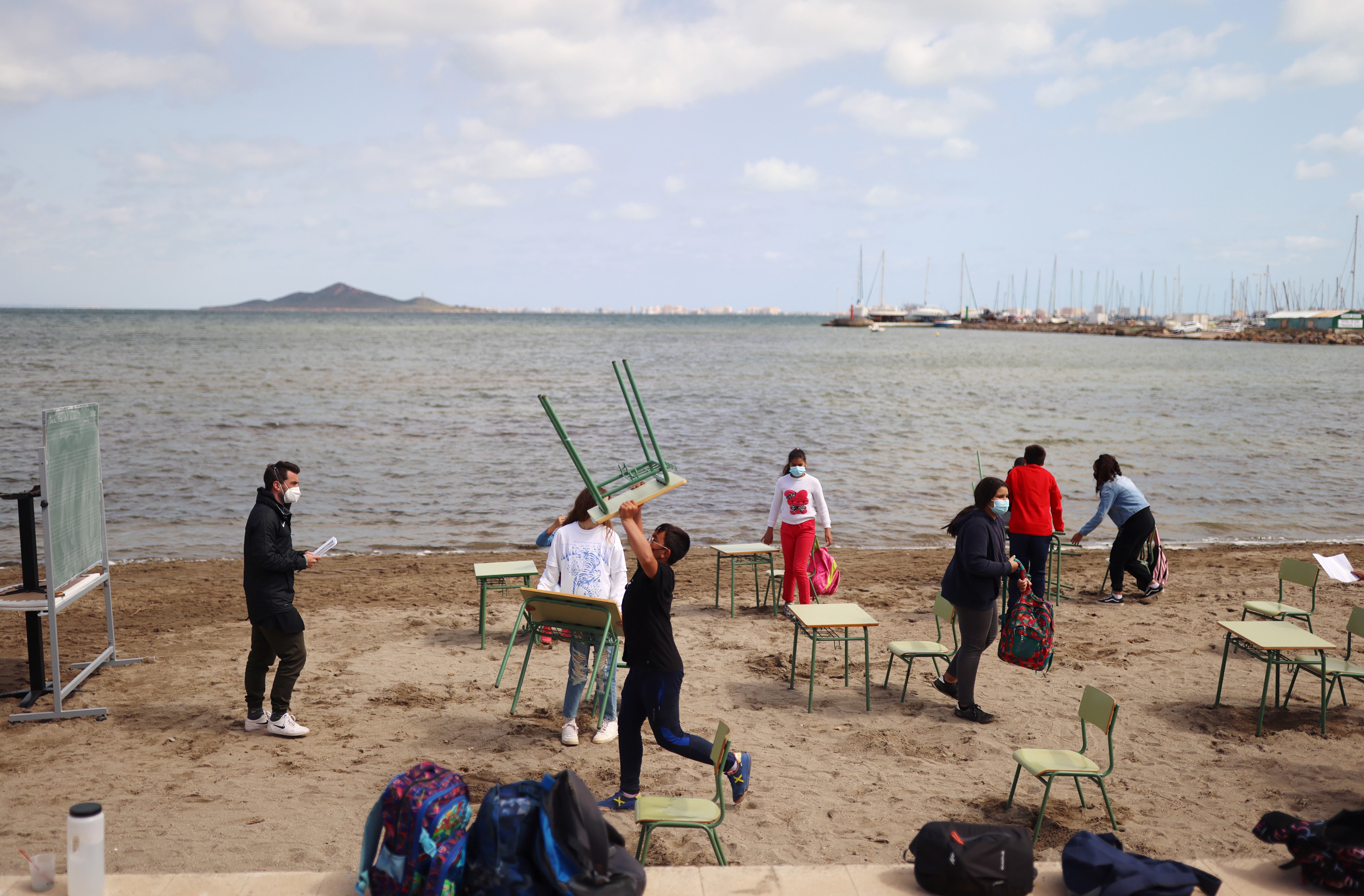 Students and teachers of the Felix Rodriguez de la Fuente school remove chairs and tables at the end of their class, as part of a project known as 'Aire Limpio' (Fresh Air) at the Playa de los Nietos (The Grandchildren's Beach), which aims to use better air quality for children during the coronavirus disease (COVID-19) pandemic, near Cartagena, southern Spain April 8, 2021. REUTERS/Nacho Doce