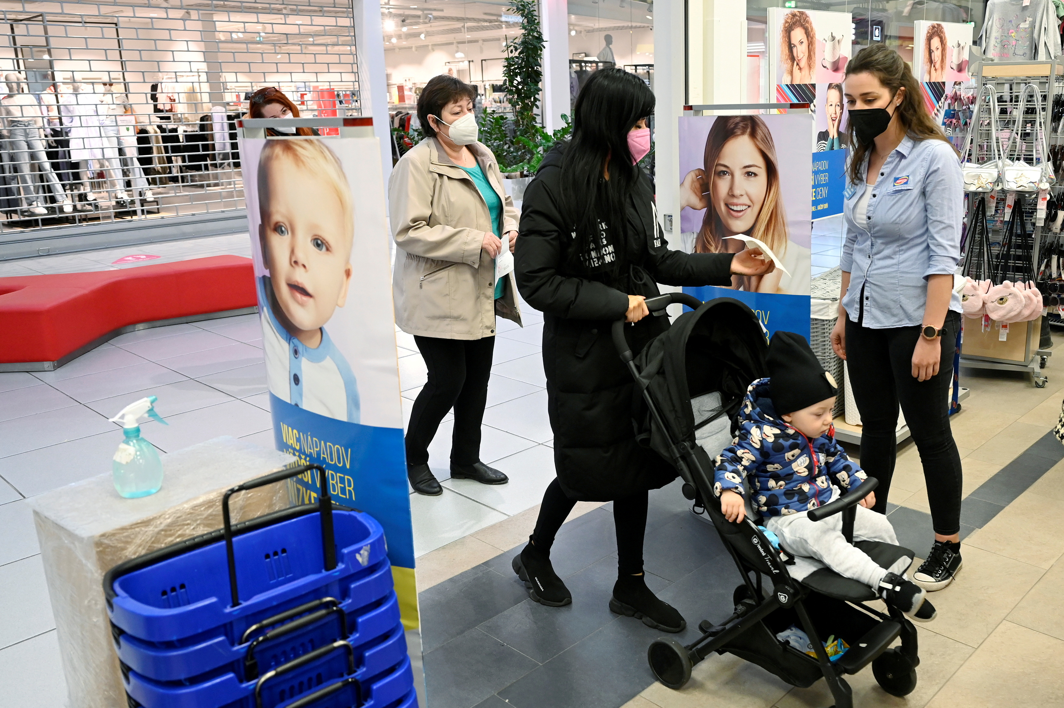 A shop assistant checks the negative COVID-19 test certificate as customers come to a store in the mall, as shops reopen after a lockdown, amid the coronavirus disease (COVID-19) pandemic in Trencin, Slovakia, April 19, 2021.  REUTERS/Radovan Stoklasa