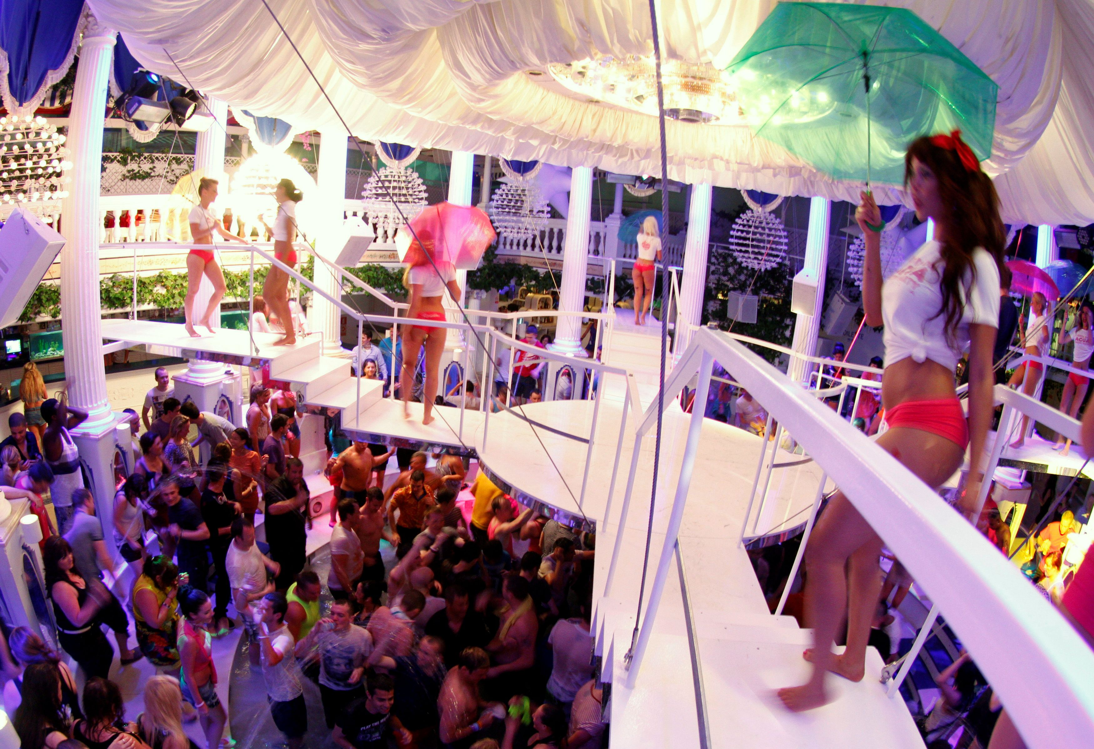 Dancers perform over the crowd during a water party inside Paradis disco in San Antonio in the Spanish Balearic island of Ibiza early June 2, 2012. REUTERS/Enrique Calvo/File Photo