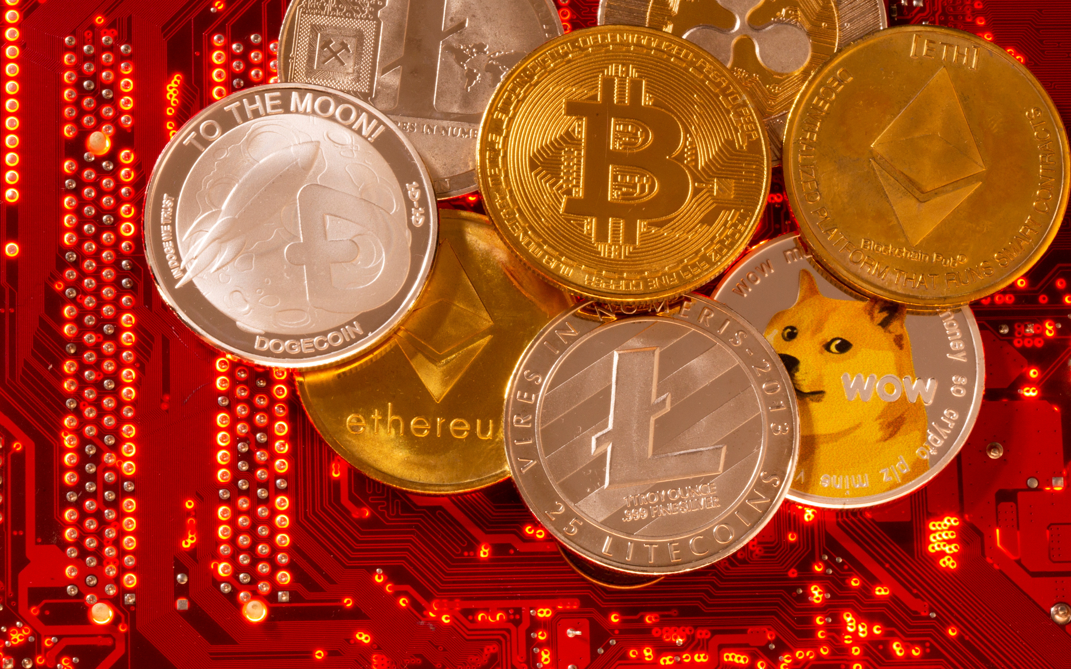 Representations of cryptocurrencies Bitcoin, Ethereum, DogeCoin, Ripple, Litecoin are placed on PC motherboard in this illustration taken, June 29, 2021. REUTERS/Dado Ruvic/Illustration/File Photo