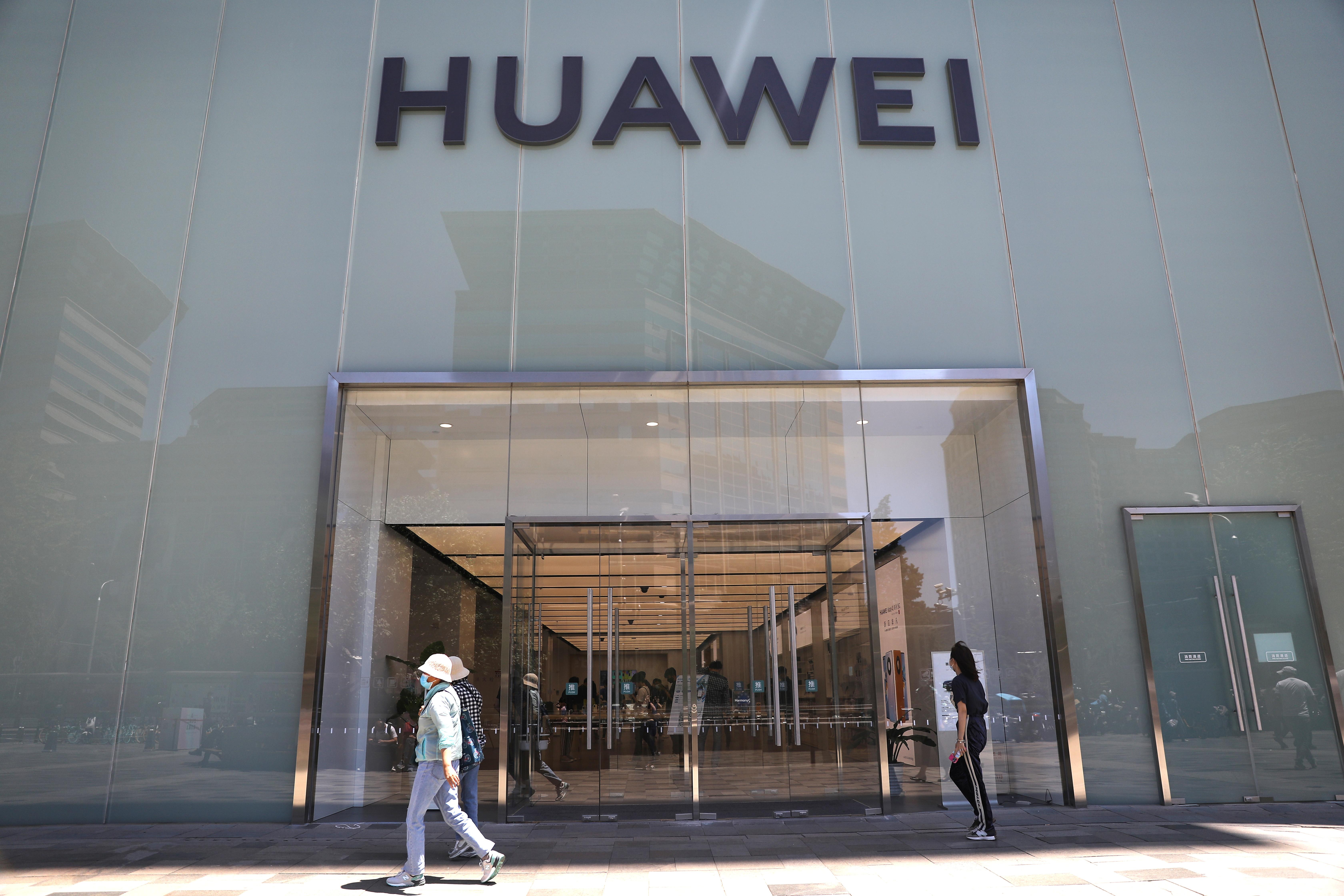People walk past a Huawei store in Beijing, China June 3, 2021. REUTERS/Tingshu Wang