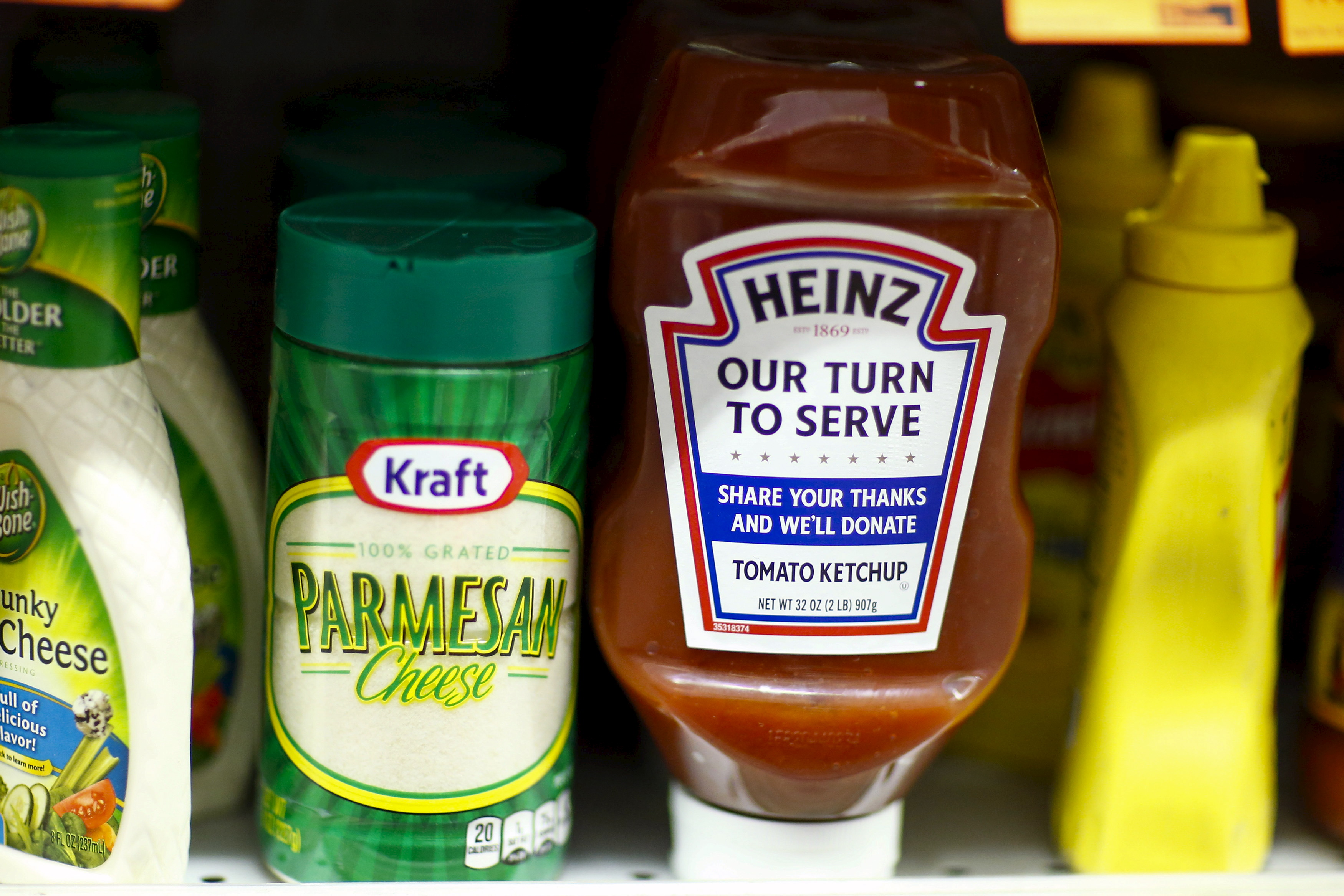 A Heinz Ketchup bottle and a bottle of Kraft parmesan cheese are displayed in a grocery store in New York March 25, 2015. Kraft Foods Group Inc, the maker of Velveeta cheese and Oscar Mayer meats, will merge with ketchup maker H.J. Heinz Co, owned by 3G Capital and Berkshire Hathaway Inc, to form the world's fifth-largest food and beverage company. REUTERS/Eduardo Munoz