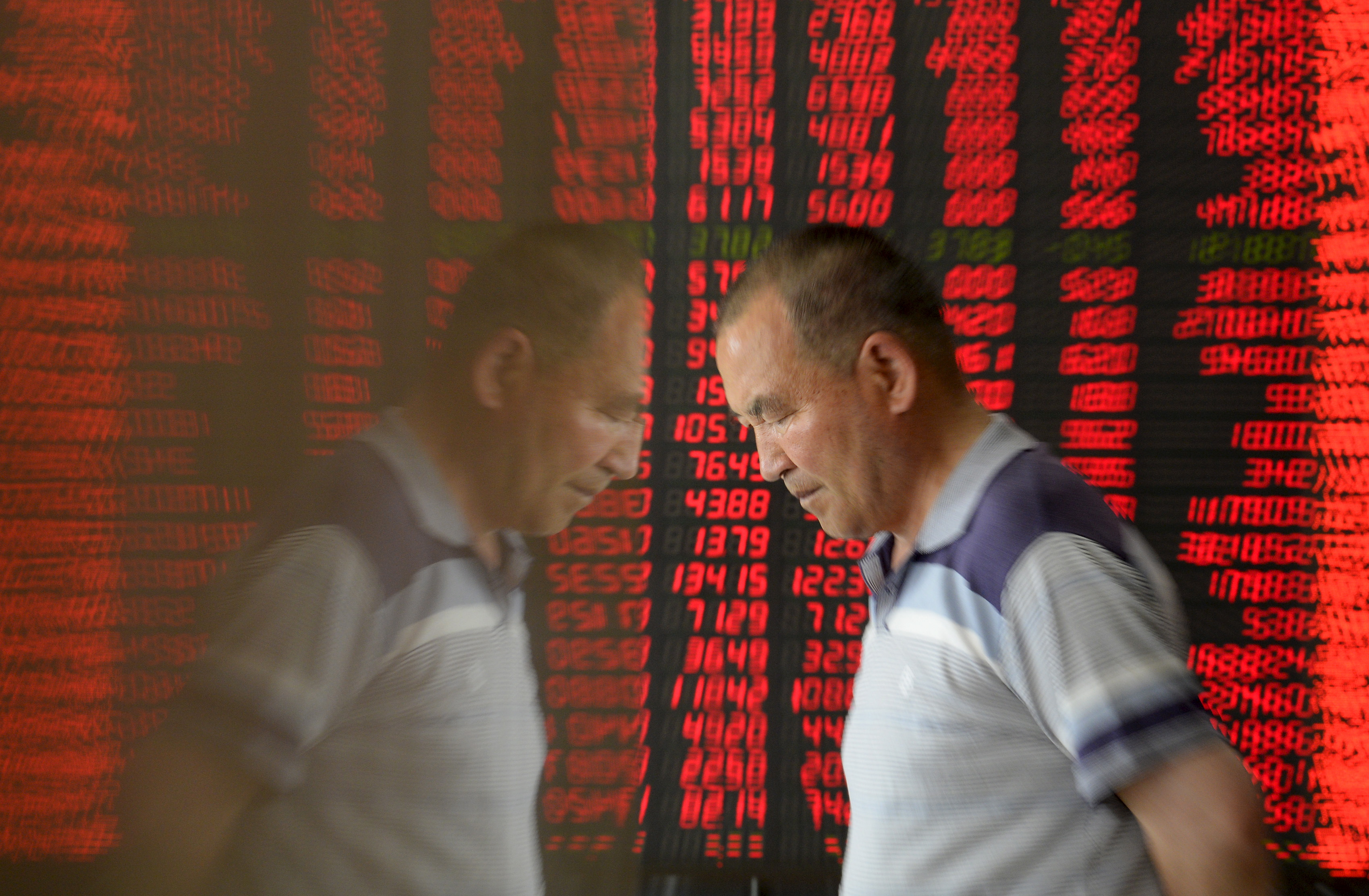 An investor is reflected on the surface of a wall as he walks past an electronic board showing stock information, filled with red figures indicating rising prices, at a brokerage house in Taiyuan, Shanxi province, China, May 27, 2015. REUTERS/Jon Woo