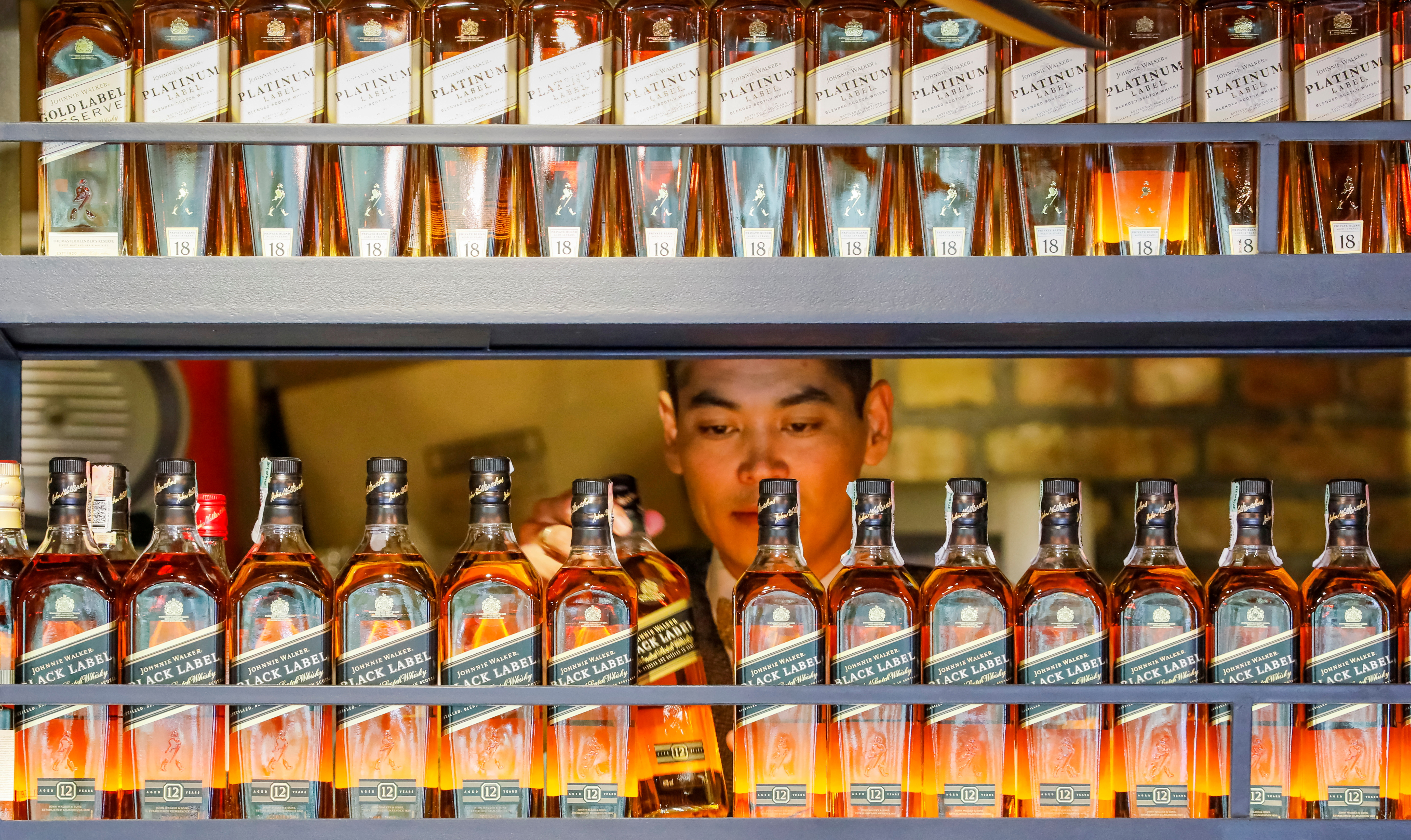 A bartender takes a bottle of Johnnie Walker whisky in Almaty, Kazakhstan June 22, 2017.  REUTERS/Shamil Zhumatov/File Photo