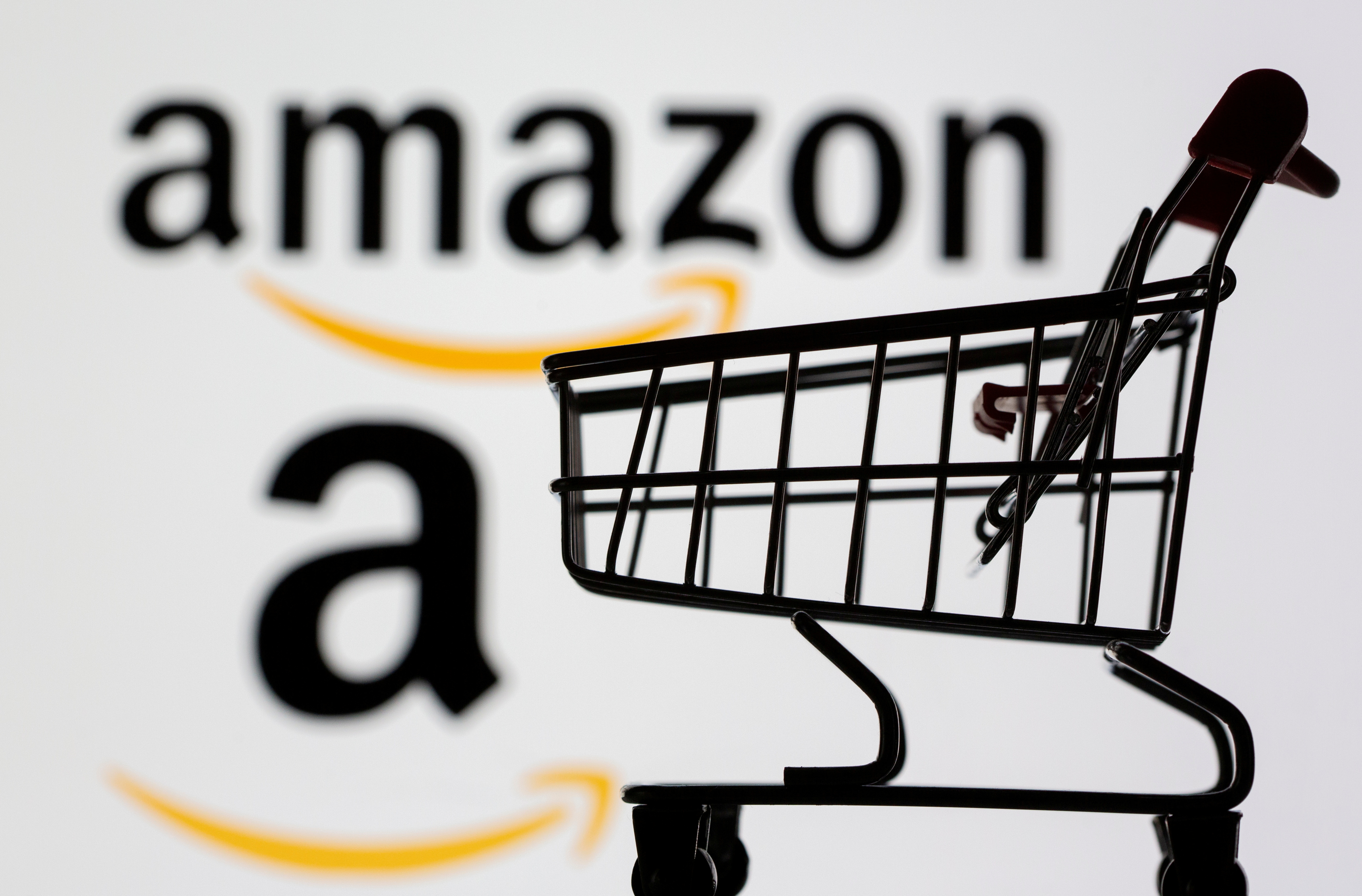 Small toy shopping cart is seen in front of displayed Amazon logo in this illustration, taken July 30, 2021. REUTERS/Dado Ruvic/Illustration/File Photo