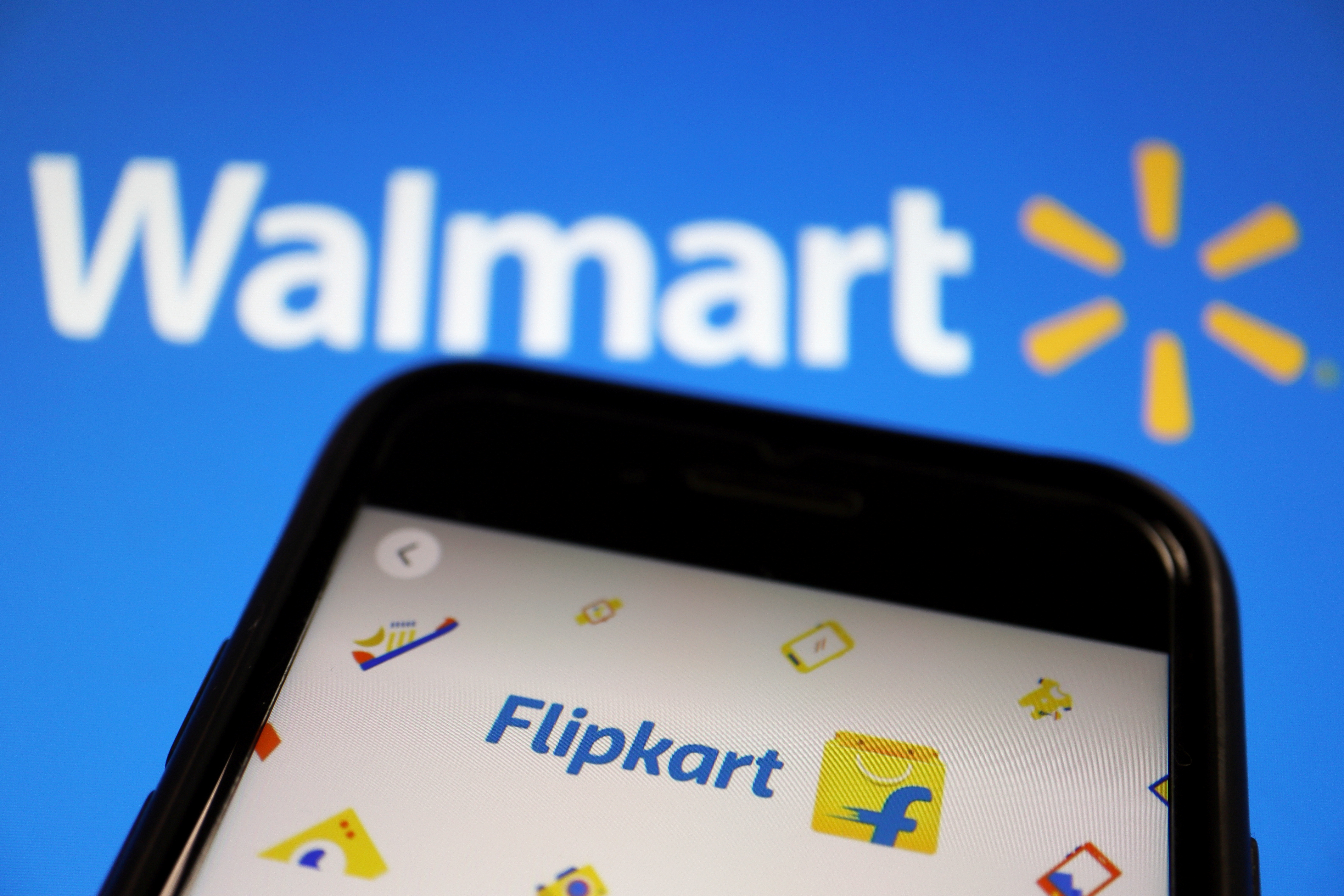 A mobile phone showing an image of Indian online retailer Flipkart is seen in front of a Walmart Inc logo displayed in this illustration picture taken July 14, 2021.