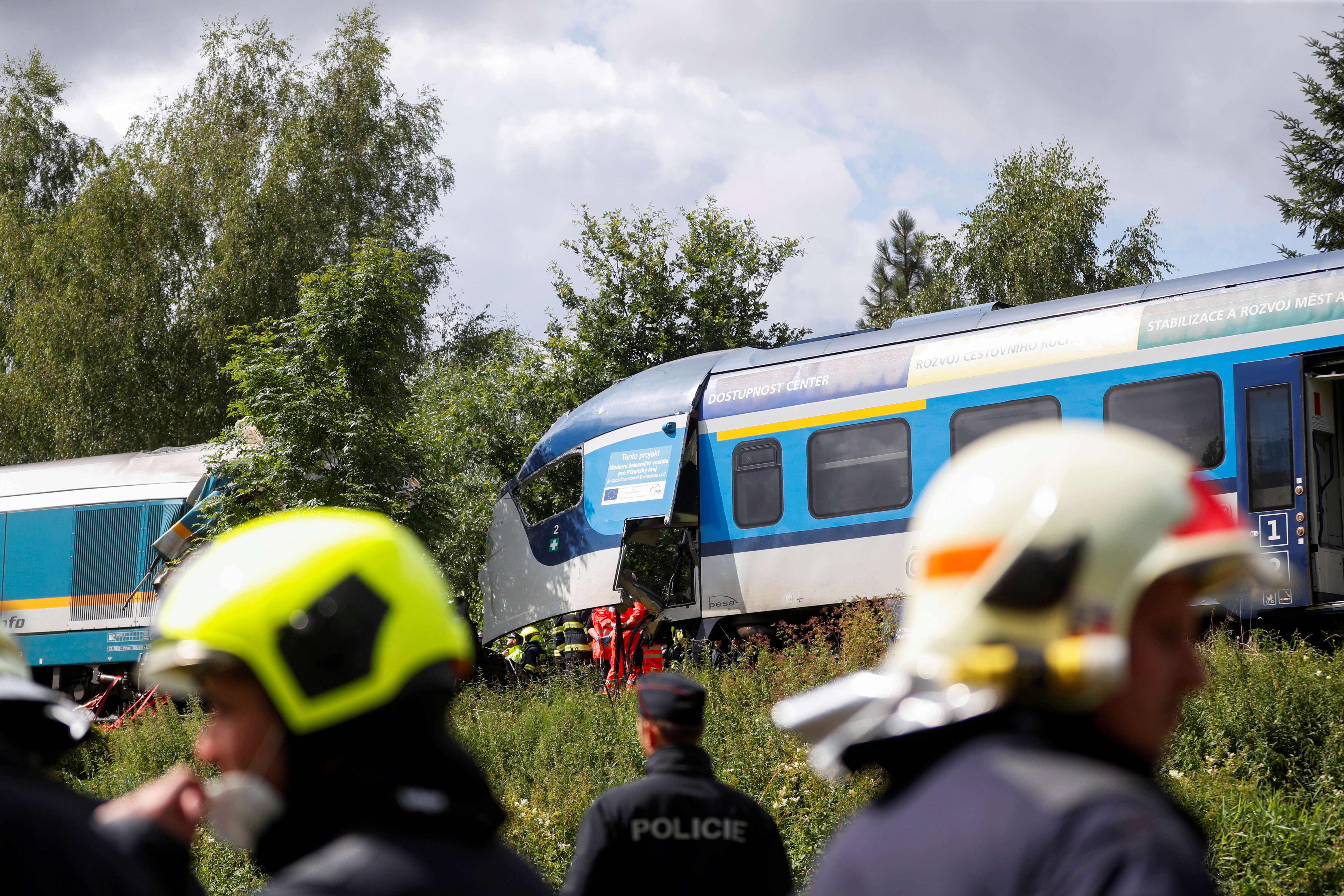 A police officer and firefighters work on a site of a train crash near the town of Domazlice, Czech Republic, August 4, 2021. REUTERS/David W Cerny