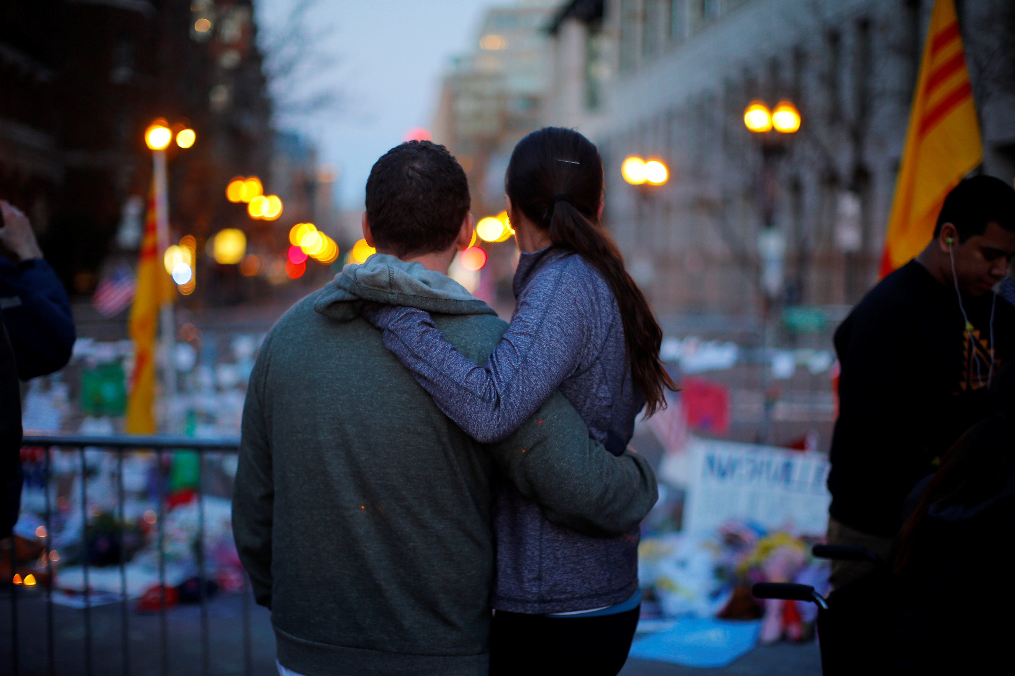A couple embraces at a memorial on Boylston Street to the victims of the Boston Marathon bombings in Boston, Massachusetts April 21, 2013. REUTERS/Brian Snyder
