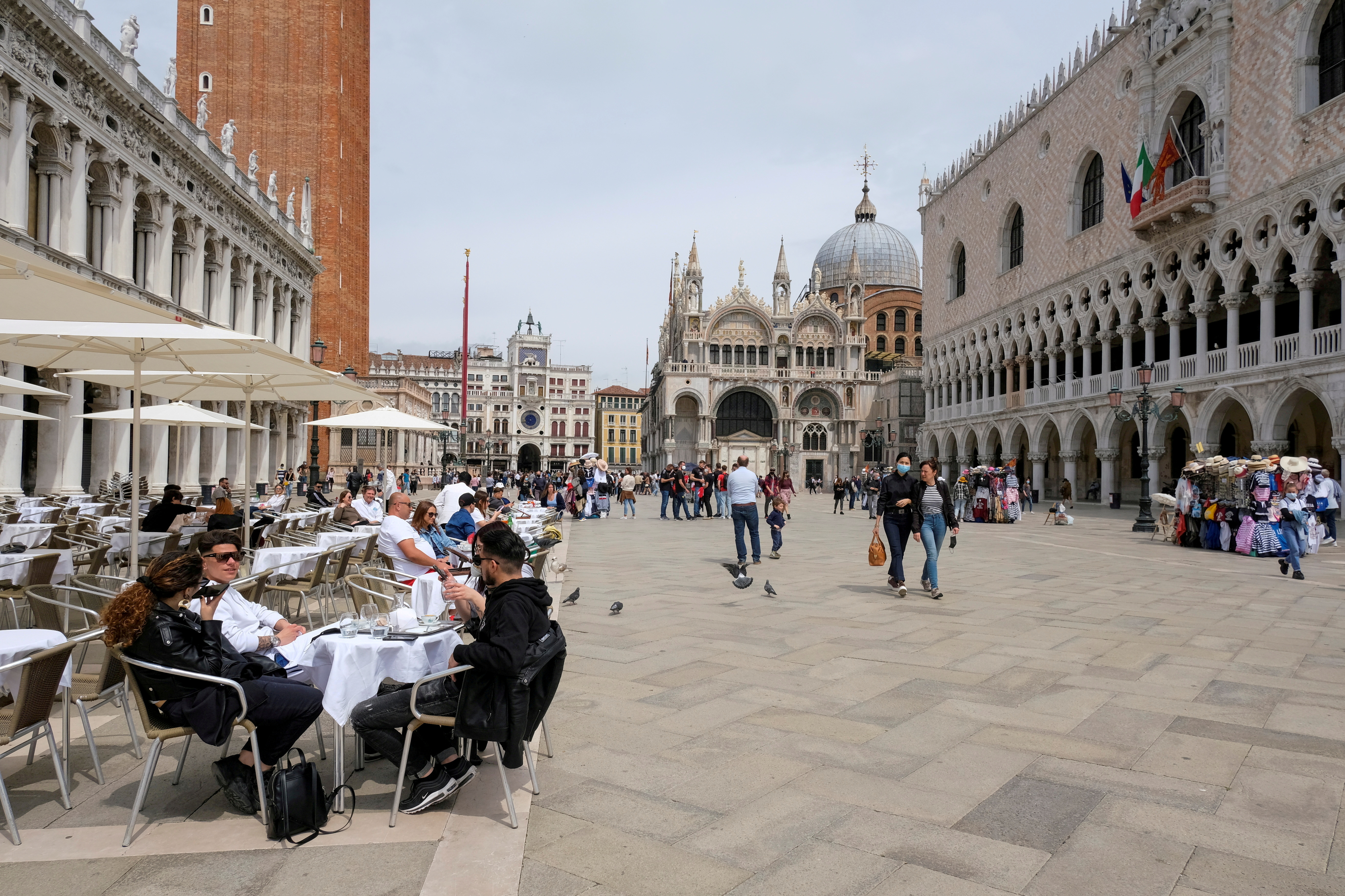 People sit at outdoor tables in St. Mark's Square, Venice, Italy, May 16, 2021. REUTERS/Manuel Silvestri