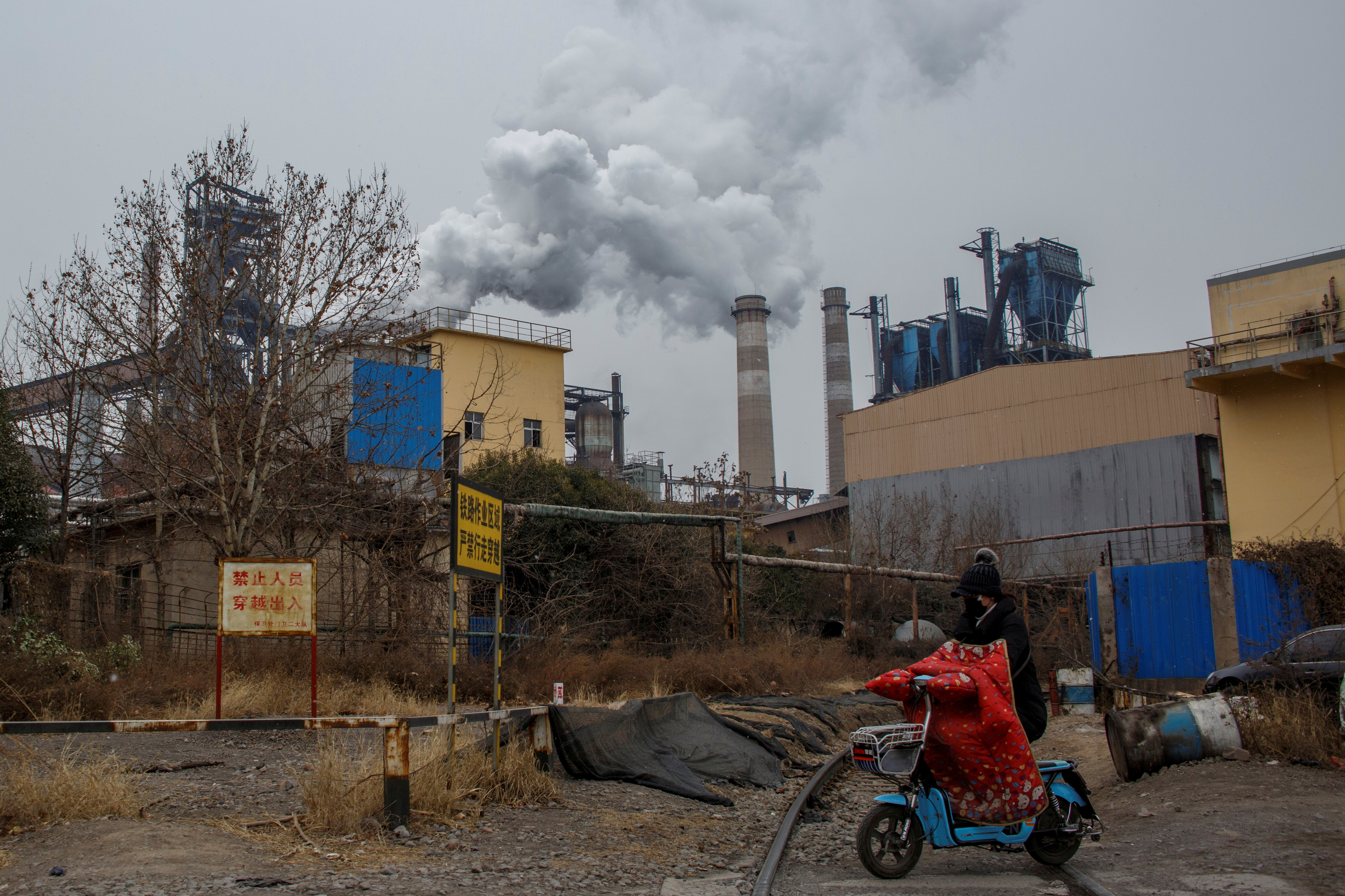 A woman rides a scooter past a steel plant in Anyang, Henan province, China, February 18, 2019. REUTERS/Thomas Peter/Files