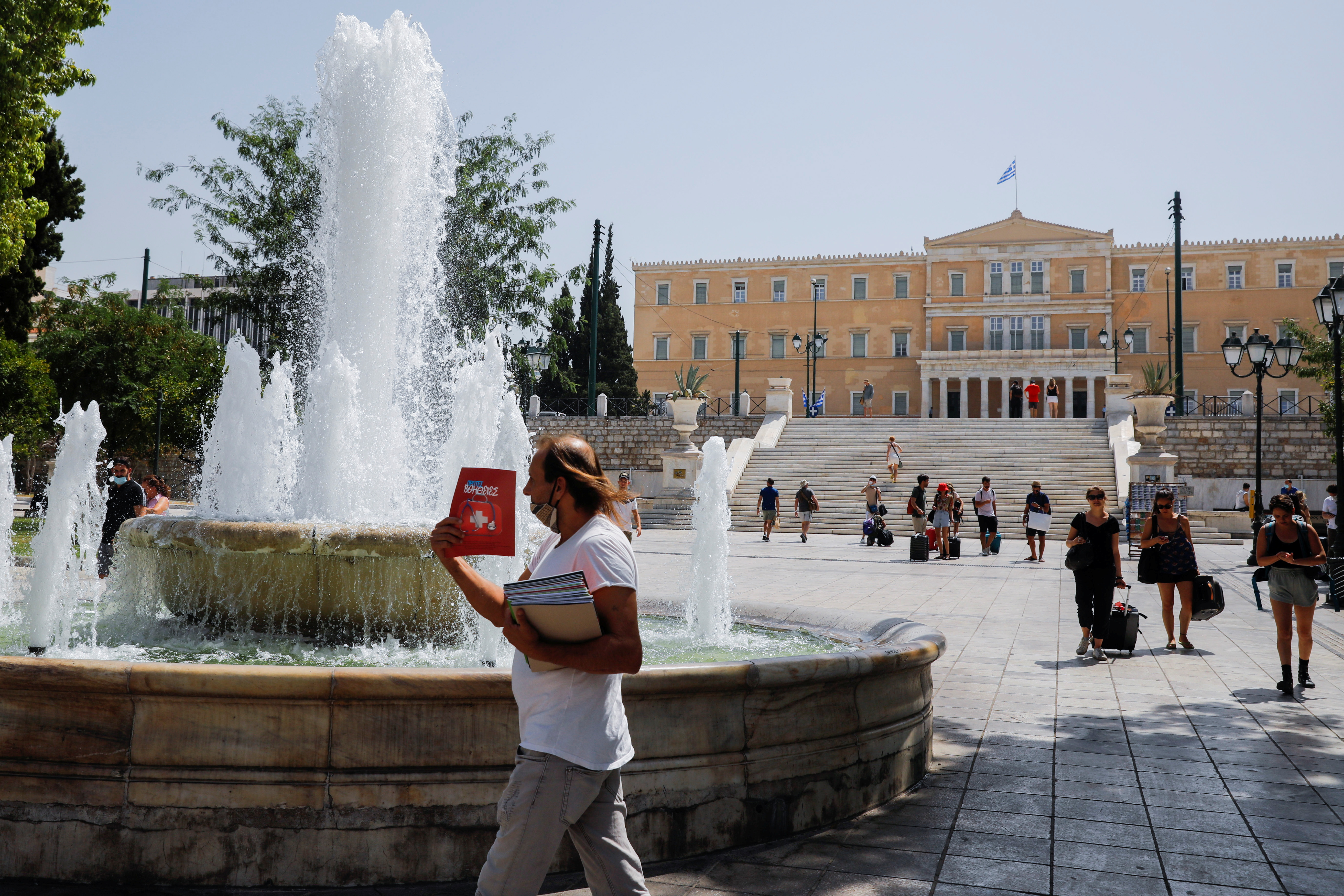 People make their way to Syntagma square during a heatwave in Athens, Greece, August 2, 2021. REUTERS/Costas Baltas