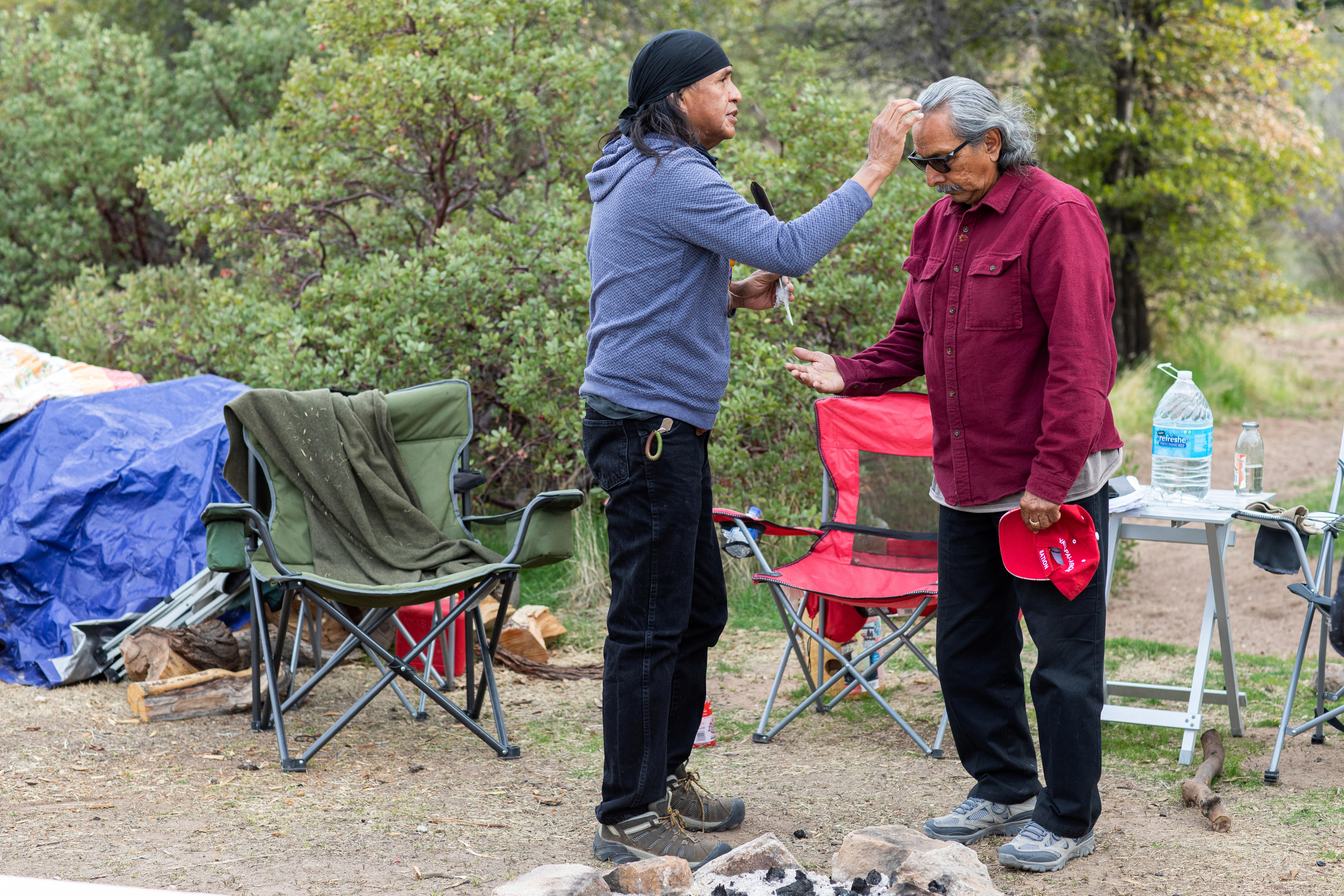 Former chairman of the San Carlos Apache Tribe Dr. Wendsler Nosie, Sr., left, prays over Daniel Mendoza at Chi'chil Bildagoteel as it is called in Apache, or Oak Flat Campground, in the Tonto National Forest near Miami, Arizona, U.S., March 29, 2021. Mendoza learned later in life that he is Chiricahua Apache and that his mom was adopted into a Mexican family. Mendoza traveled from San Diego to visit Oak Flat and meet fellow Chiricahua Apache Dr. Nosie after hearing about the fight to defend the land that many Apache people hold sacred. Picture taken March 29, 2021.  REUTERS/Caitlin O'Hara