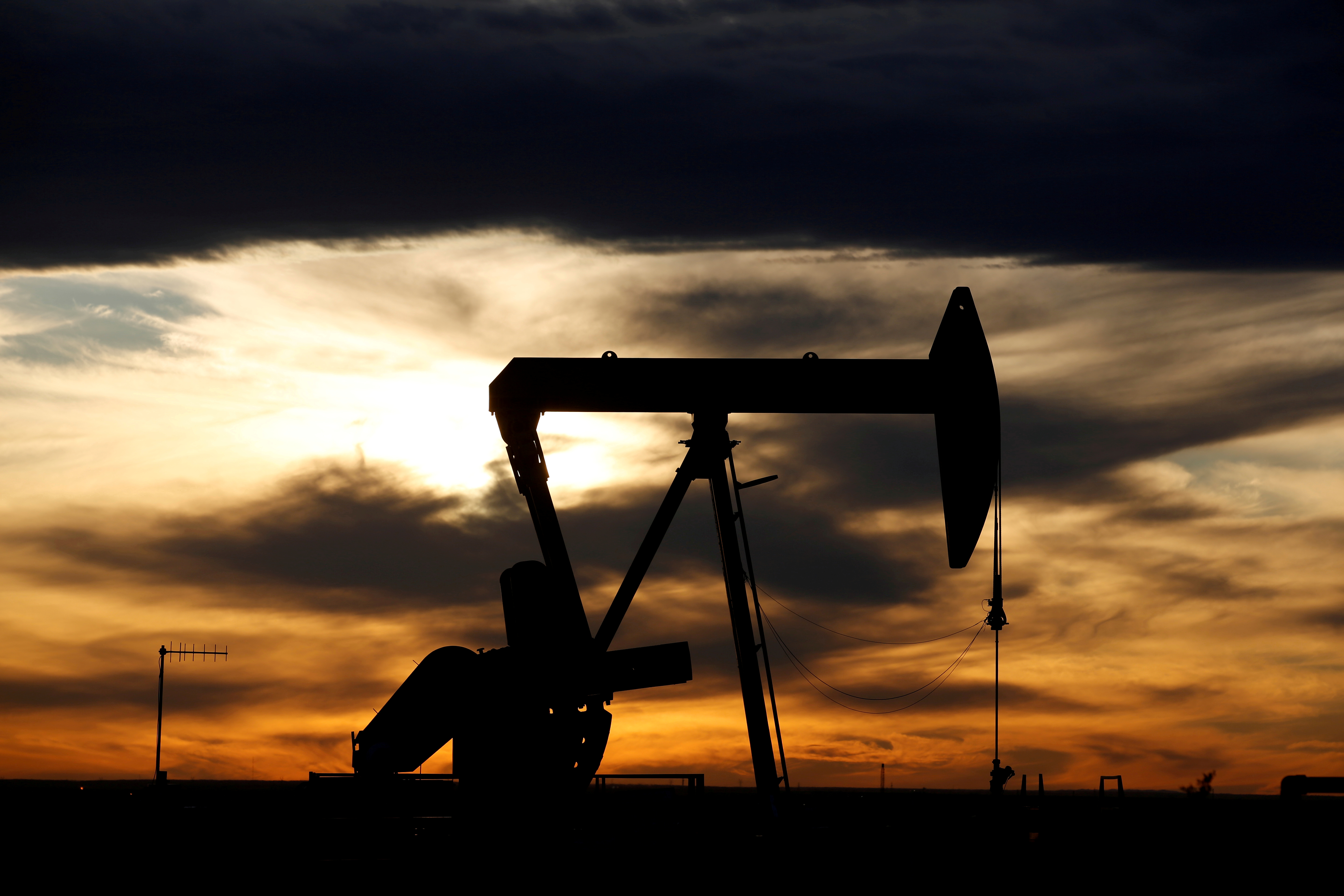 The sun sets behind a crude oil pump jack on a drill pad in the Permian Basin in Loving County, Texas, U.S. November 24, 2019. REUTERS/Angus Mordant/File Photo