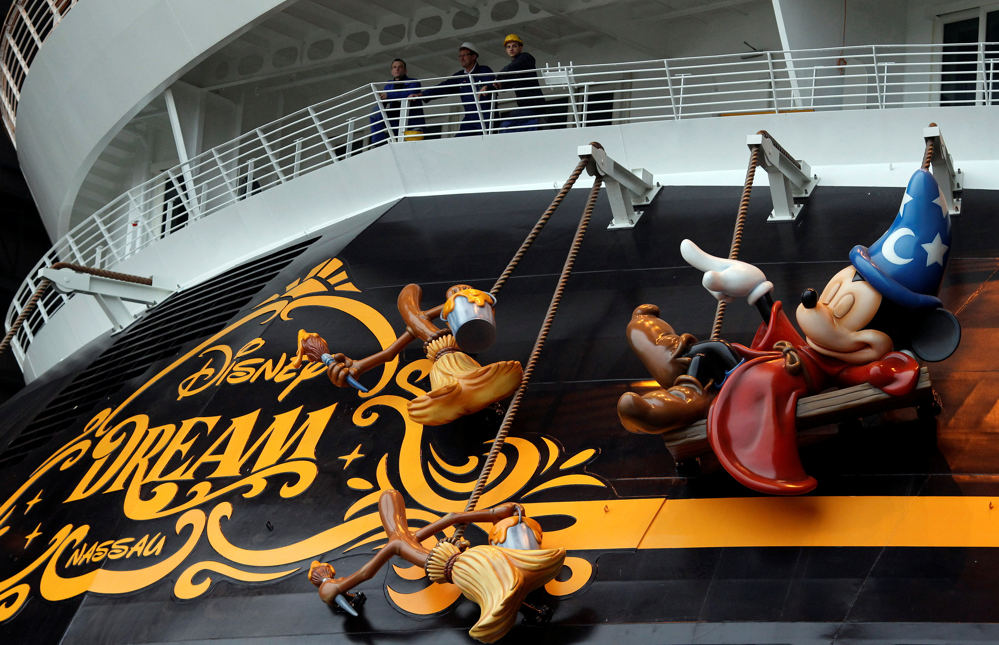 Workers stand on the deck of  the newly built cruise ship
