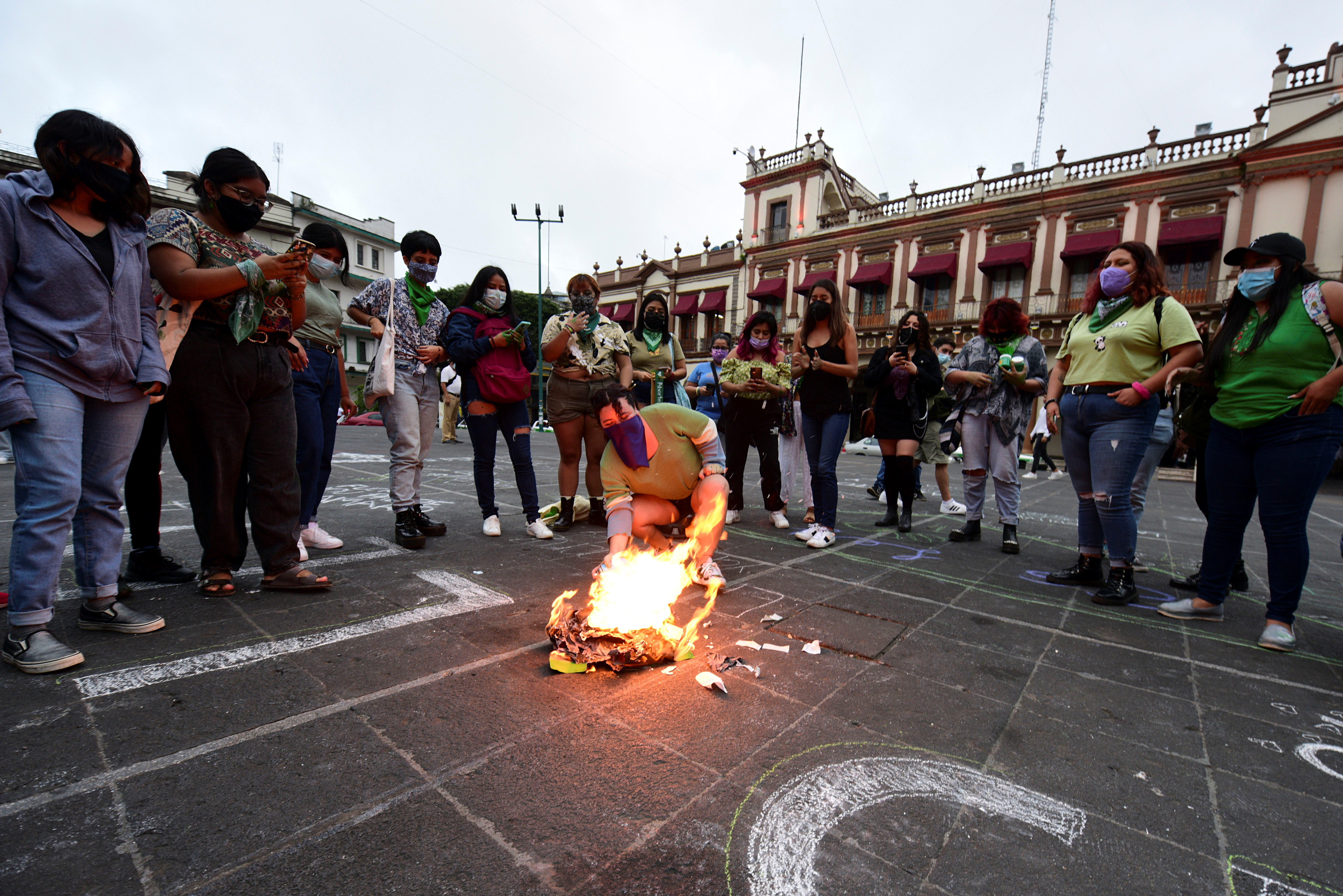 A woman burns papers as she celebrates that Veracruz became the fourth state in Mexico to clear away criminal penalties for elective abortion after lawmakers voted to decriminalize the procedure, at Plaza Lerdo in Xalapa, Mexico July 20, 2021. REUTERS/Oscar Martinez