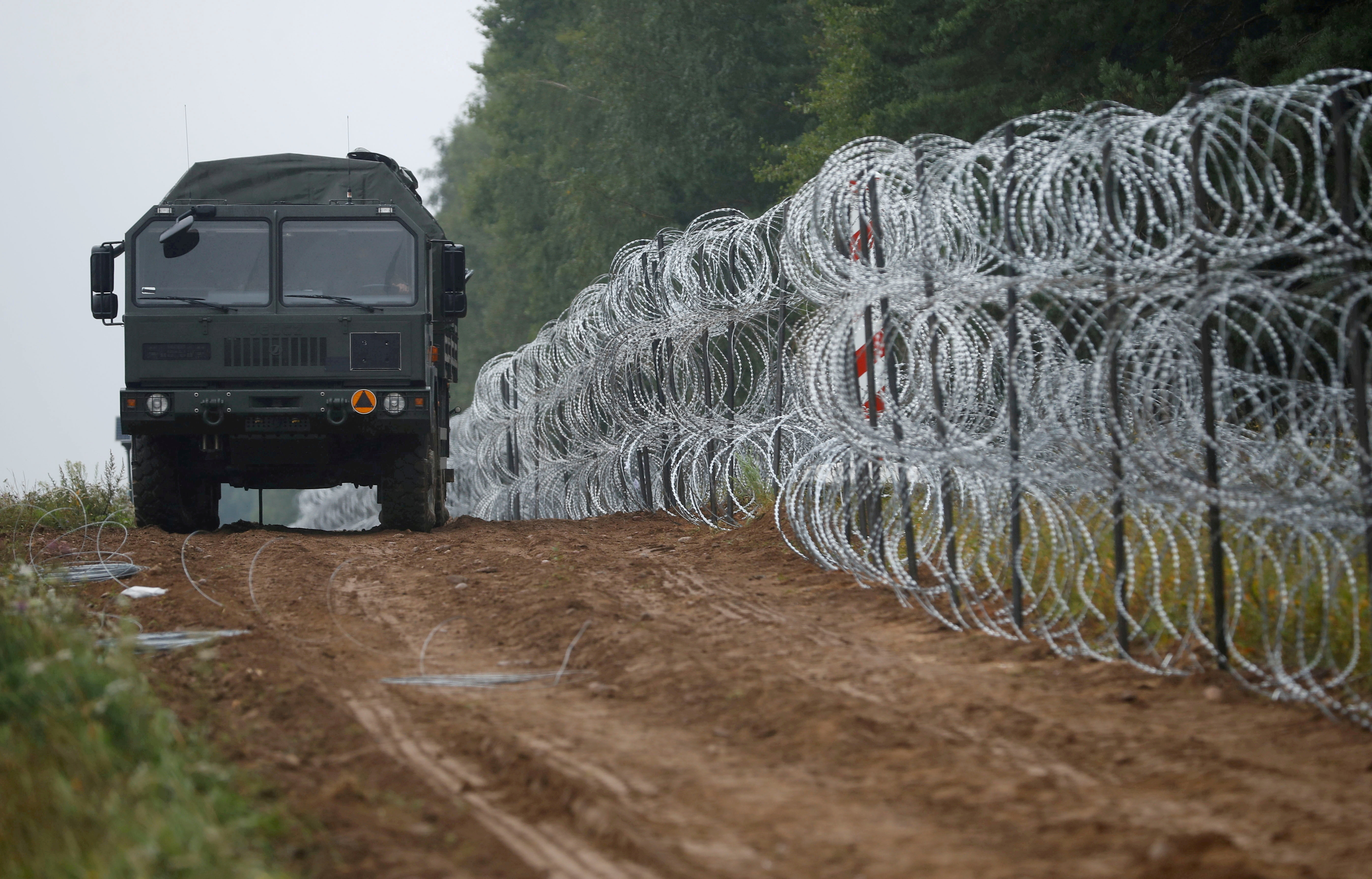 A view of a vehicle next to a fence built by Polish soldiers on the border between Poland and Belarus near the village of Nomiki, Poland August 26, 2021. REUTERS/Kacper Pempel/File Photo