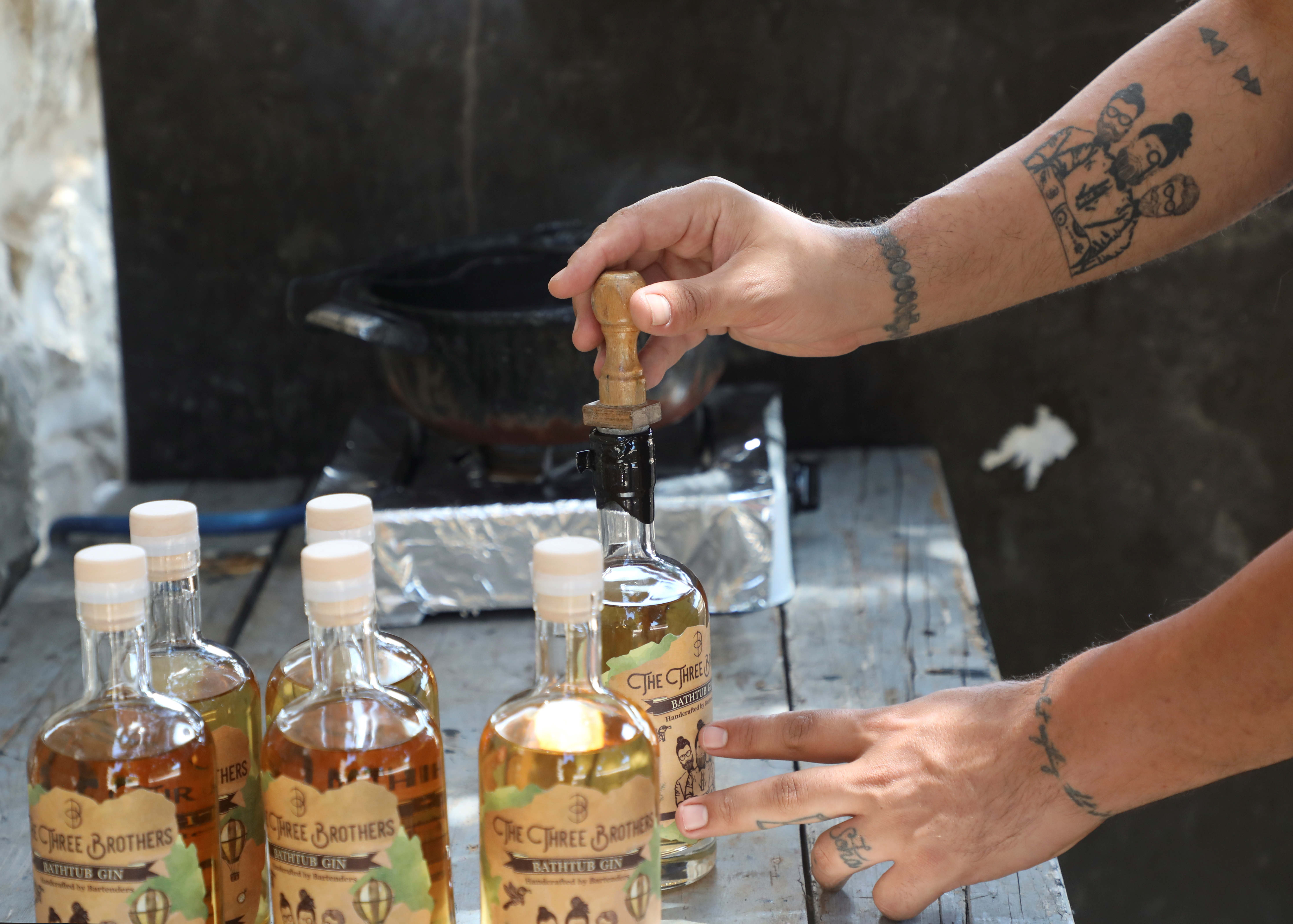 Ralph Malak, one of the founders and chief taste developer of the Three Brothers distillery, stamps a gin bottle in Smar Jbeil, Lebanon June 15, 2021.  REUTERS/Mohamed Azakir