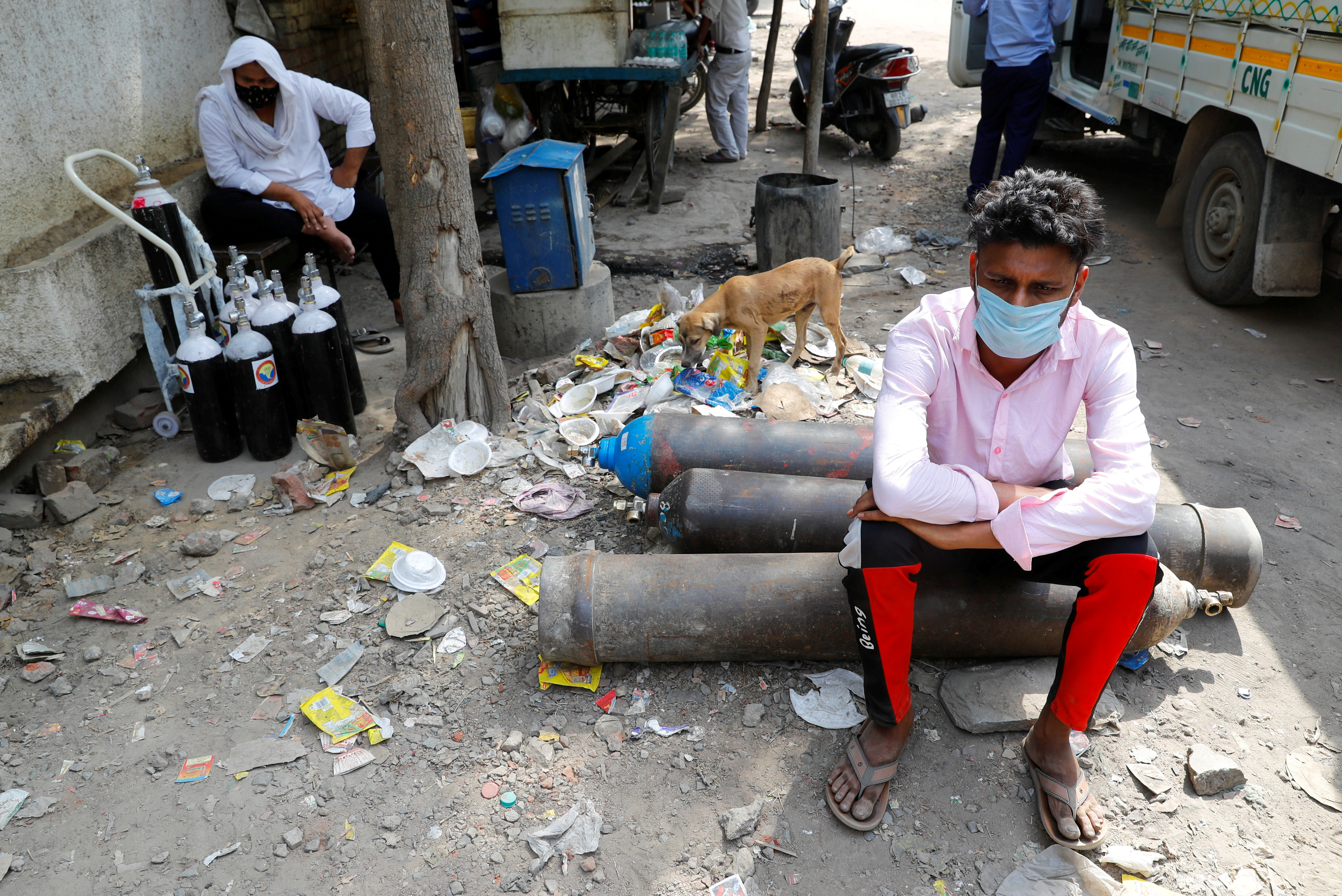 Sumit Kumar, 28, sits on an oxygen cylinder as he waits outside a factory to get it refilled, amidst the spread of the coronavirus disease (COVID-19) in New Delhi, India, April 28, 2021. REUTERS/Adnan Abidi/File Photo