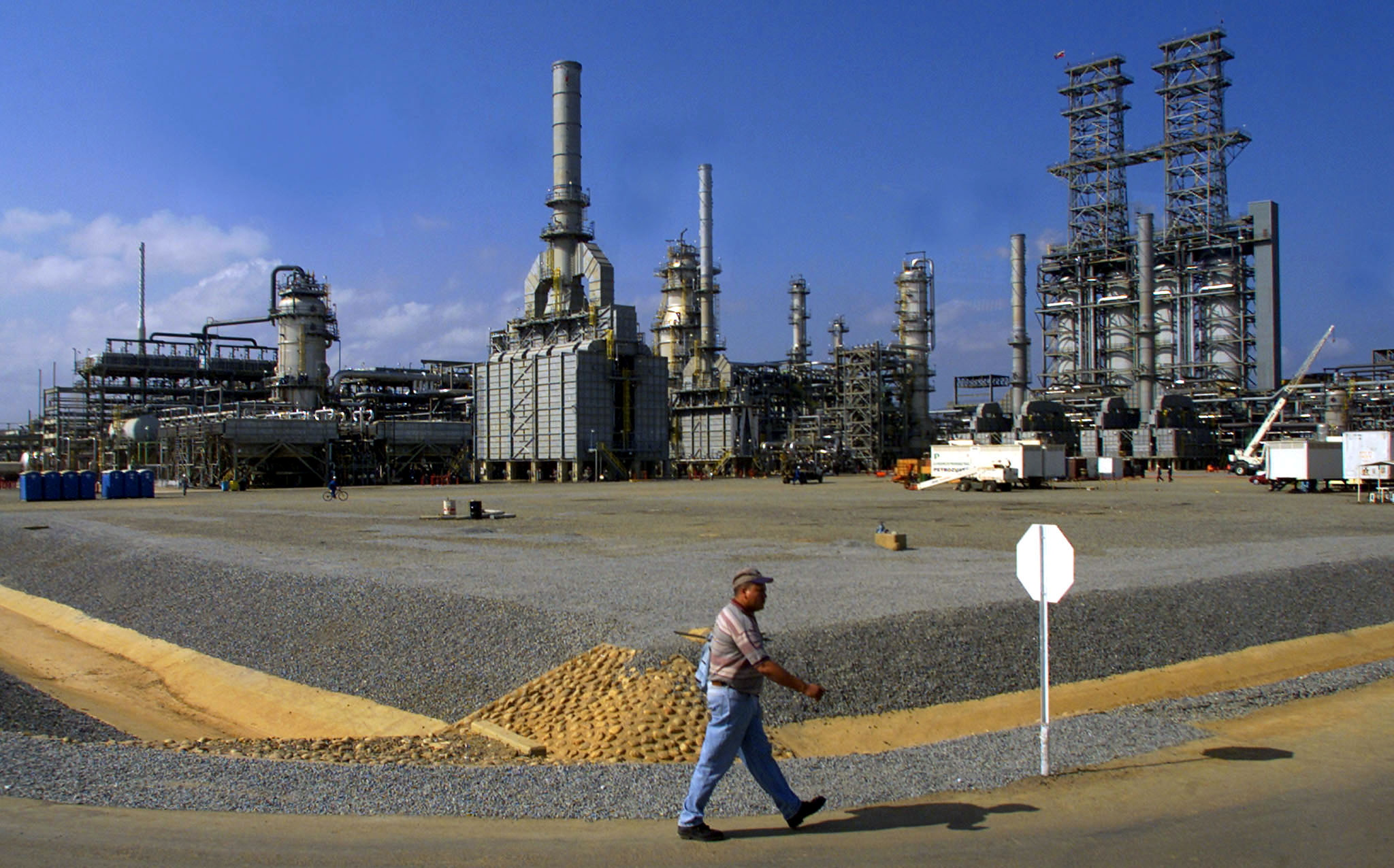 A worker walks past the Petrozuata Oil Refinery in the Orinoco oil belt in the Venezuelan eastern state of Anzoategui, February 13, 2001.U.S. oil company ConocoPhillips had sought up to $22 billion from PDVSA for the broken contracts and loss of future profits from the Hamaca and Petrozuata oil projects.