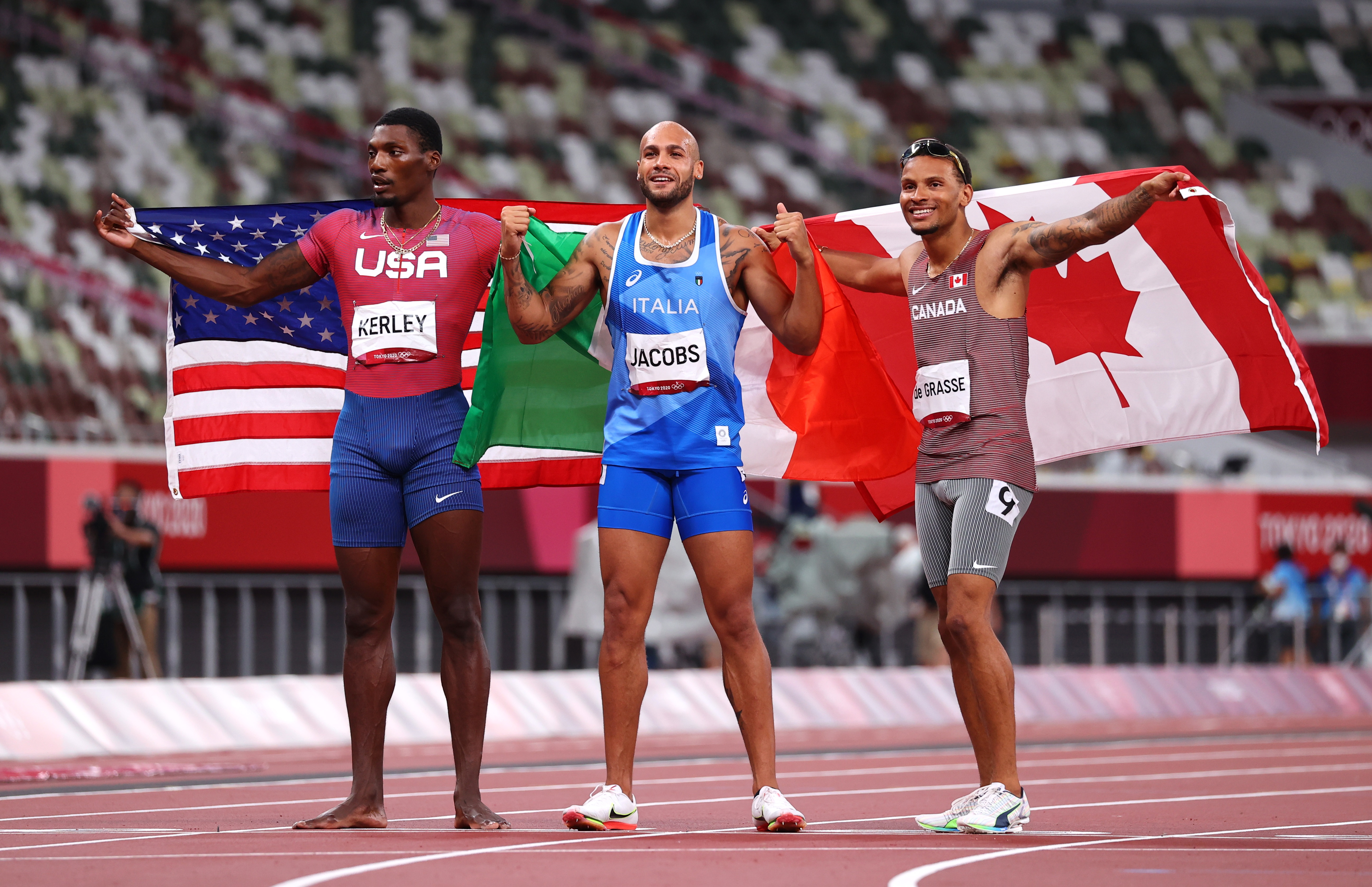 Tokyo 2020 Olympics - Athletics - Men's 100m - Final - OLS - Olympic Stadium, Tokyo, Japan - August 1, 2021. Gold medalist Lamont Marcell Jacobs of Italy celebrates with silver medalist Fred Kerley of the United States and bronze medalist Andre de Grasse REUTERS/Lucy Nicholson