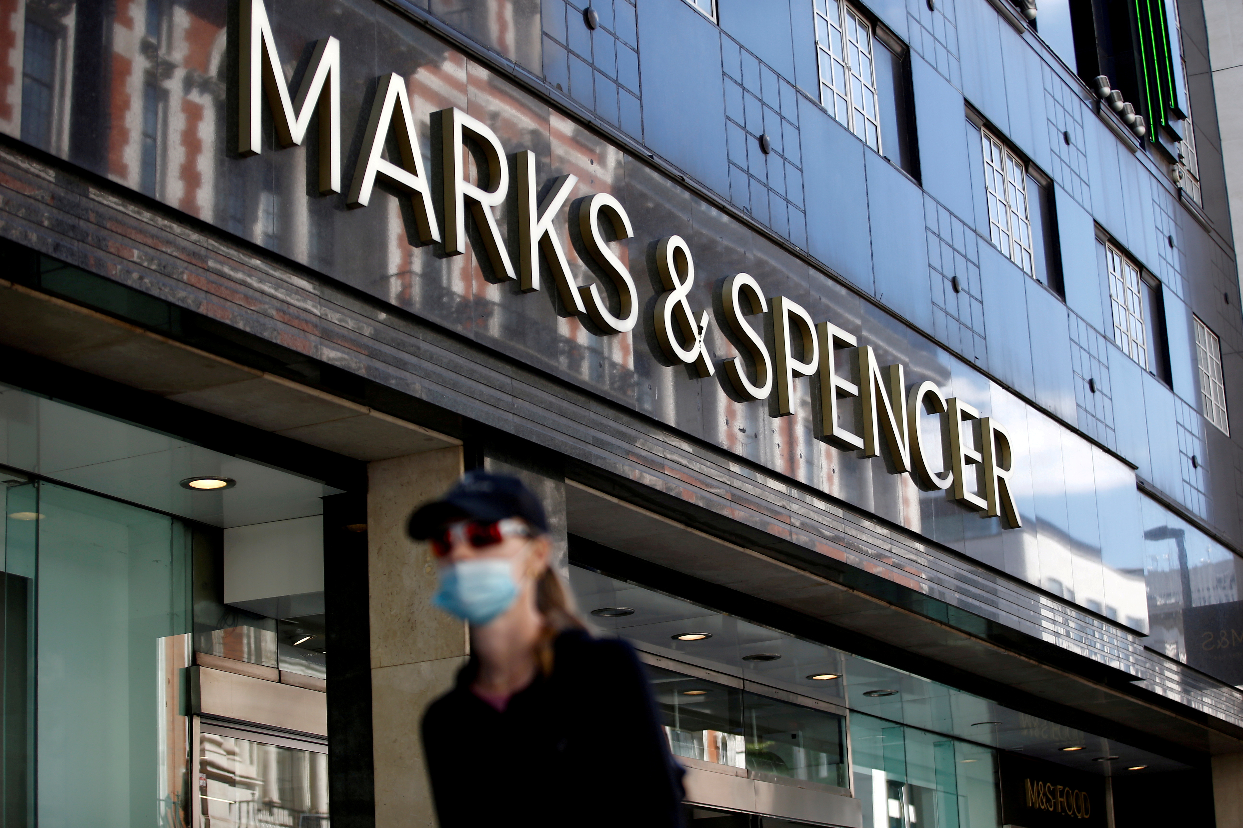 A woman walks past a Marks & Spencer store on Oxford Street, amid the outbreak of the coronavirus disease (COVID-19), in London, Britain, July 20, 2020. REUTERS/Henry Nicholls