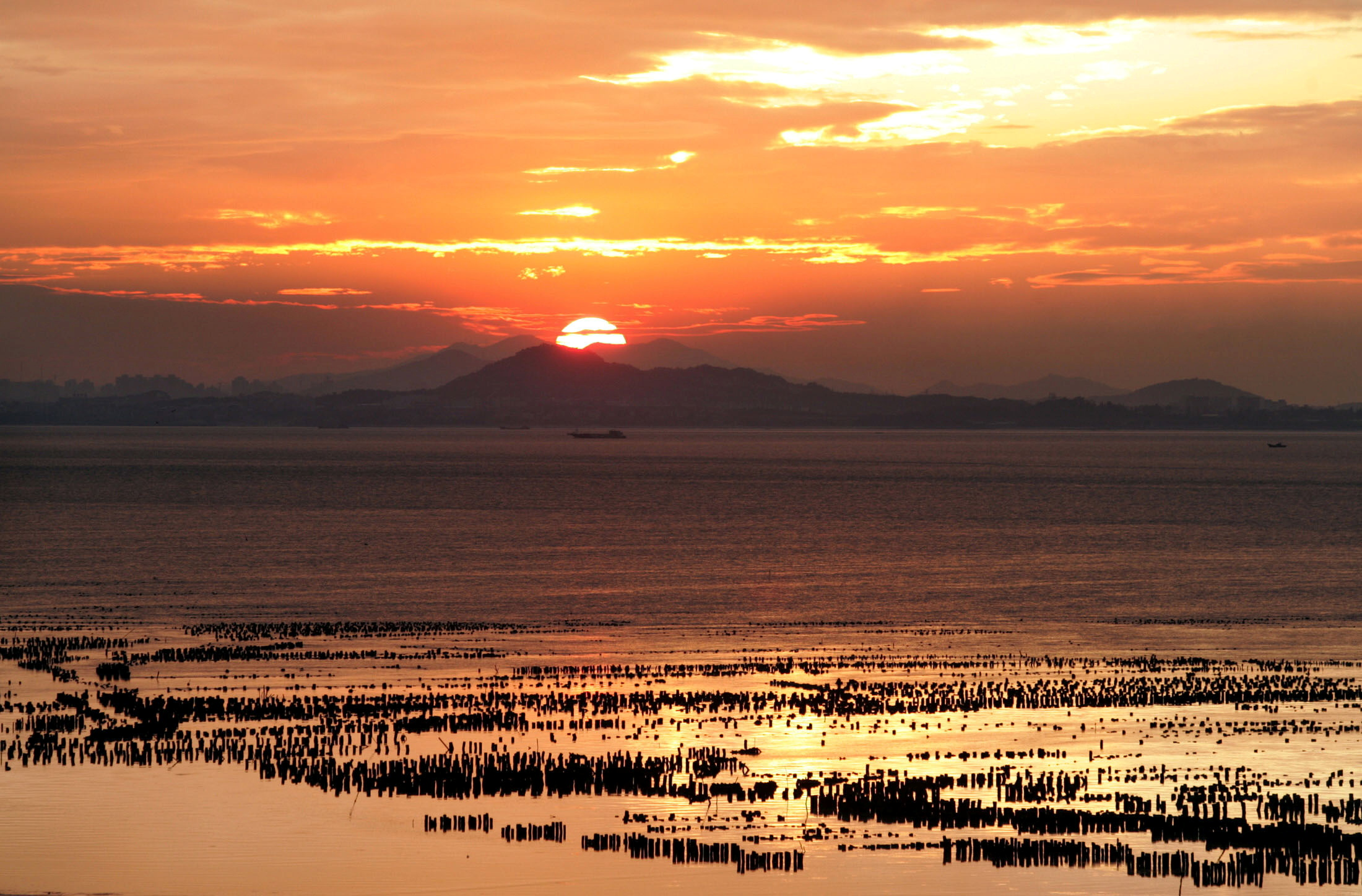 The sun sets over China's southeastern coast of Fujian as seen from Taiwan's frontline island of Kinmen on September 11, 2004. REUTERS/Richard Chung
