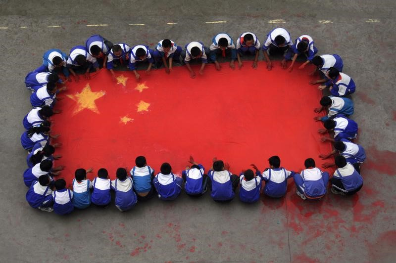 Pupils create the national flag on a canvas by using their hands dipped in red paint at a primary school in Jinan, Shandong province September 14, 2009. China will celebrate the 60th anniversary of its founding on October 1 this year. REUTERS/Stringer